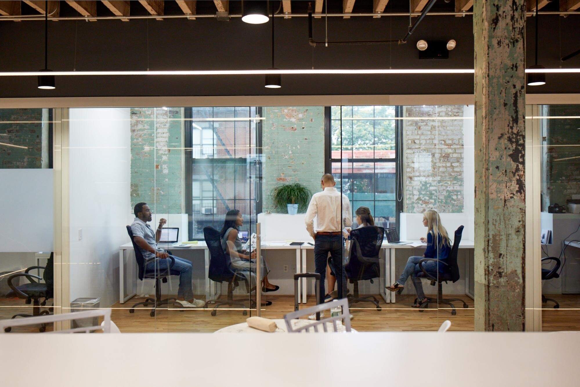 four employees at a shared desk office space