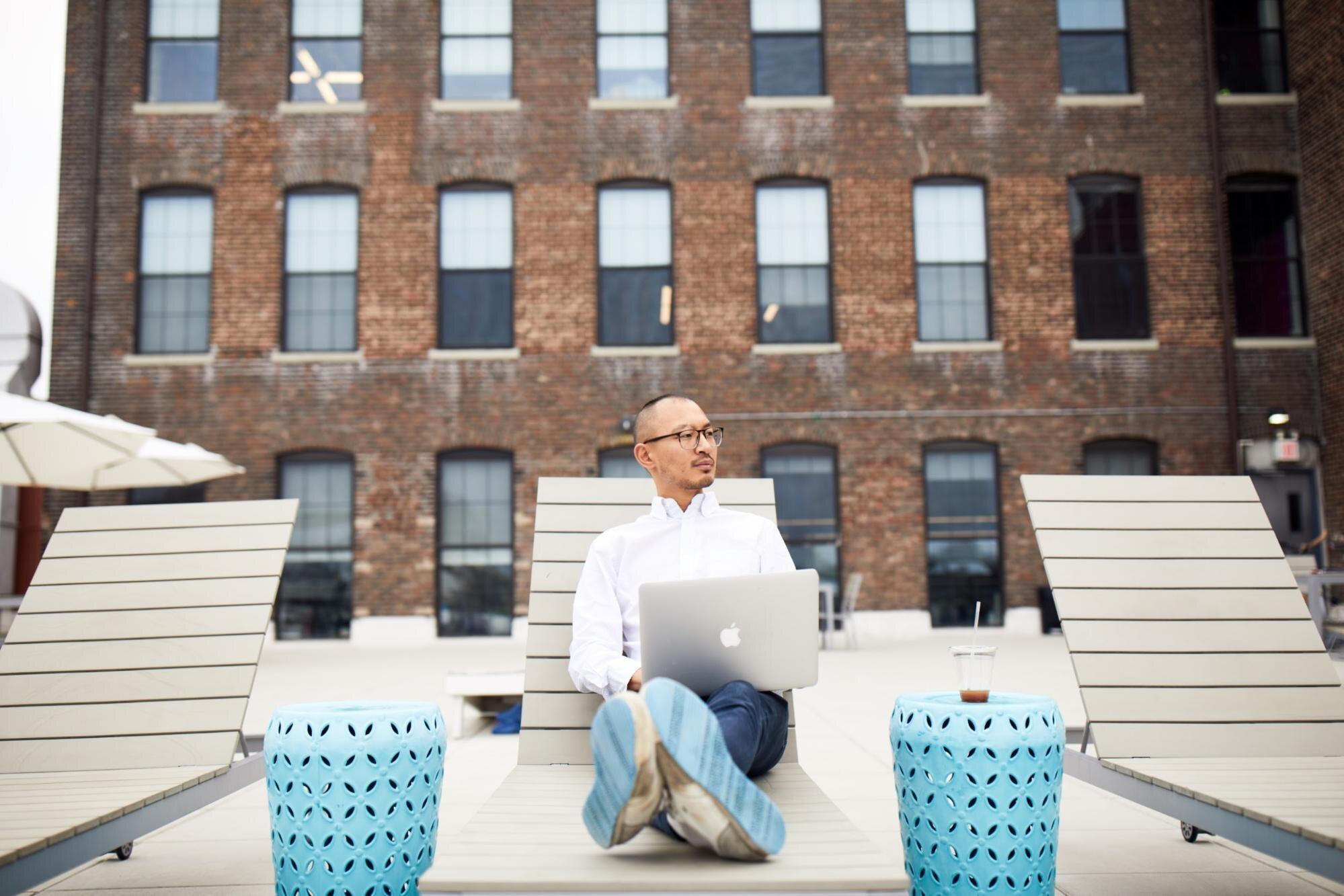 Man enjoying working from outside pool lounge area
