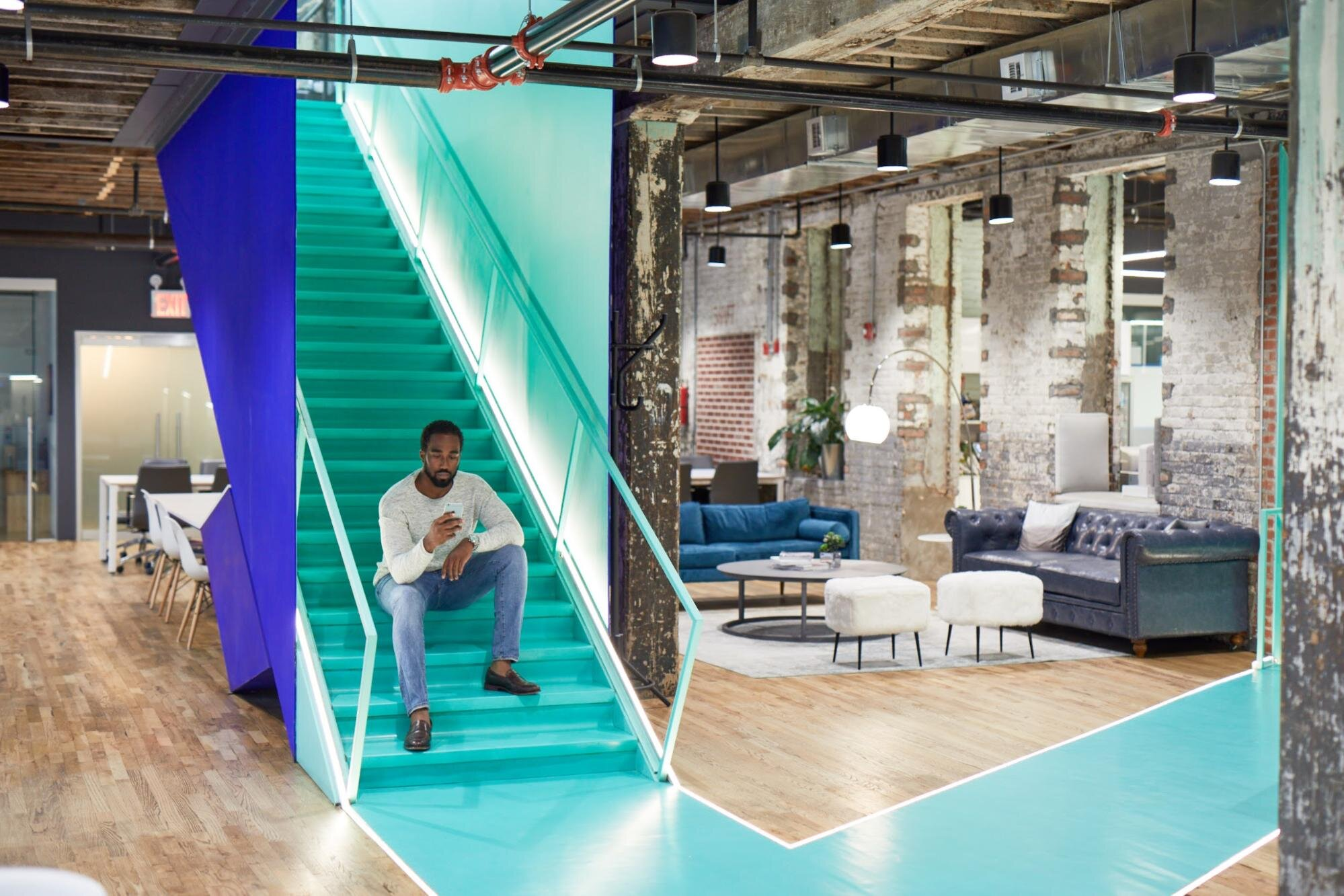 Man sitting on the stairs of a bond collective office space