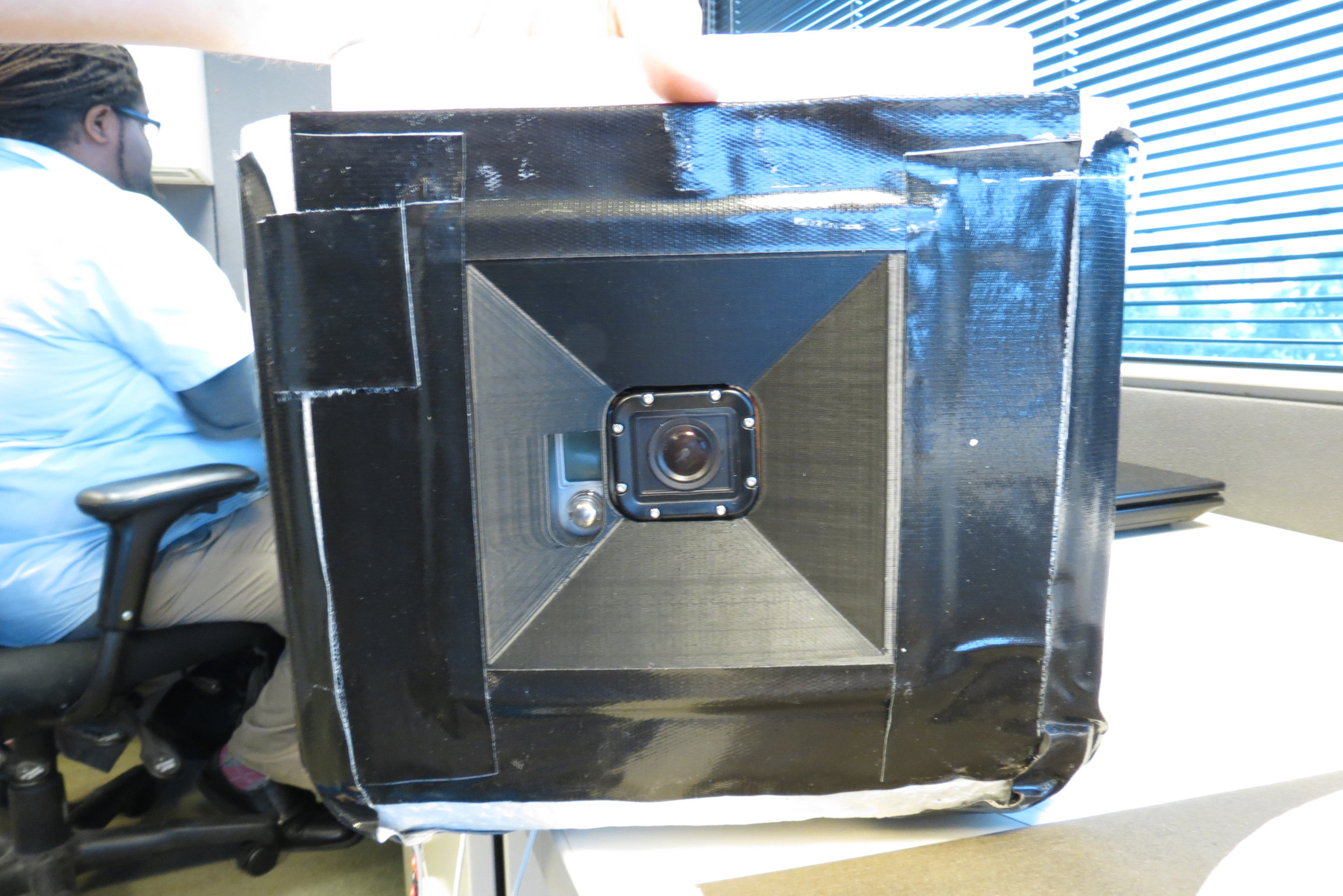 3D printed camera holder, glued and taped into side of foam cooler.