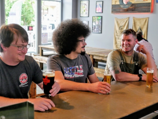 L-R. Former head brewers Shaun Salyards, Cory Carvatt, and current head brewer Greg Moore share a pint.