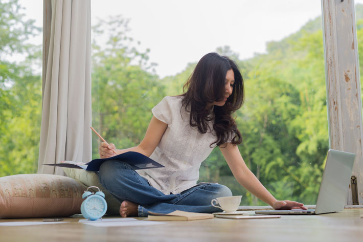 Woman sitting on the floor writing