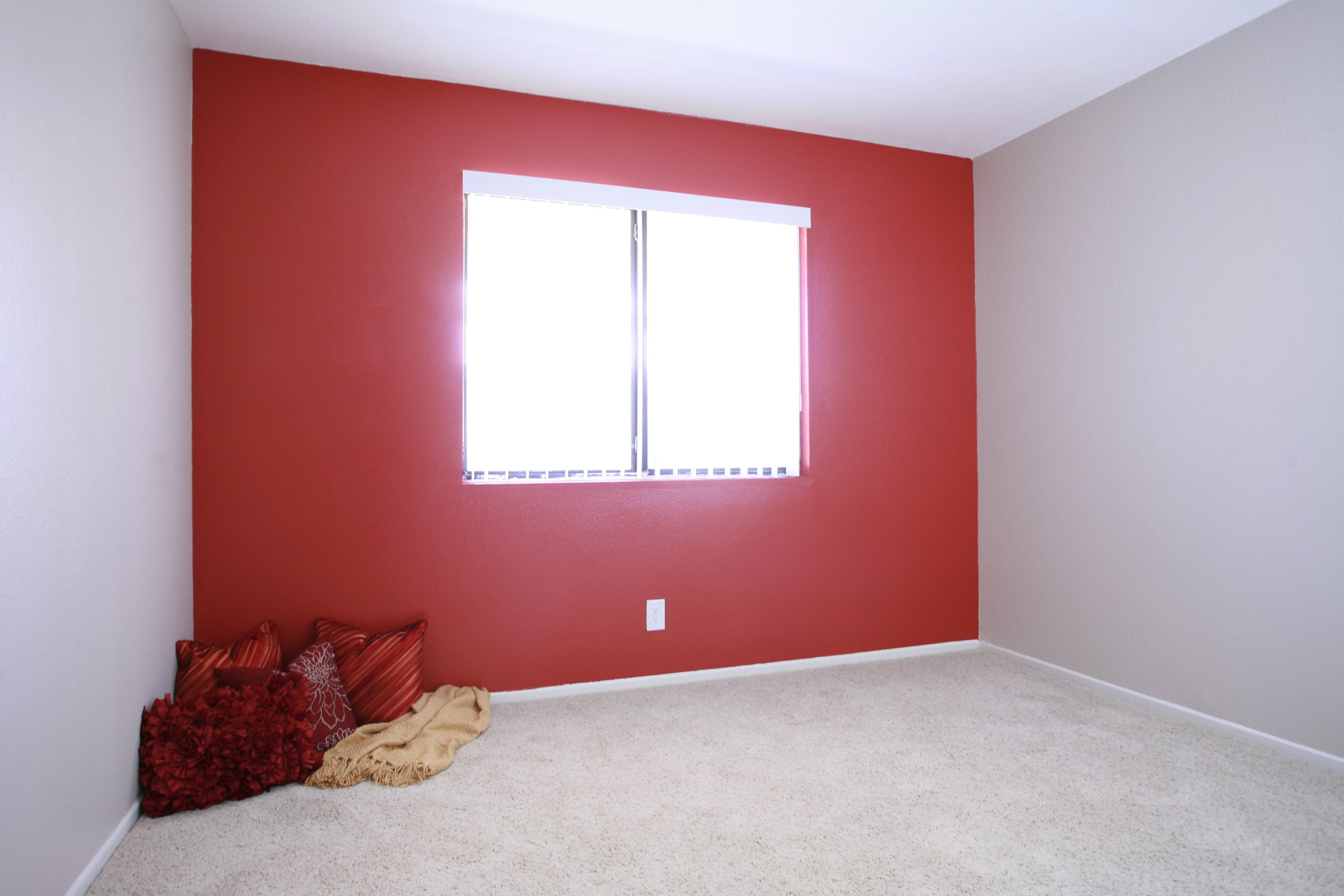 Red accent wall in bedroom at Serrano