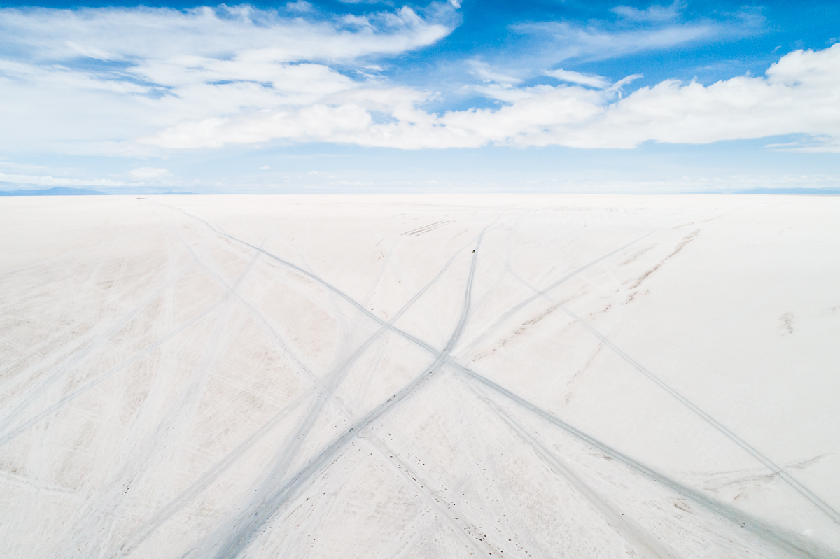 blue-white-salar-de-uyuni-salt-flats-potosi-bolivia-car-tracks-vast-expanse-desert-vastness-jeep-4x4-wheel-drive-road-roadtrip-south-america.jpg