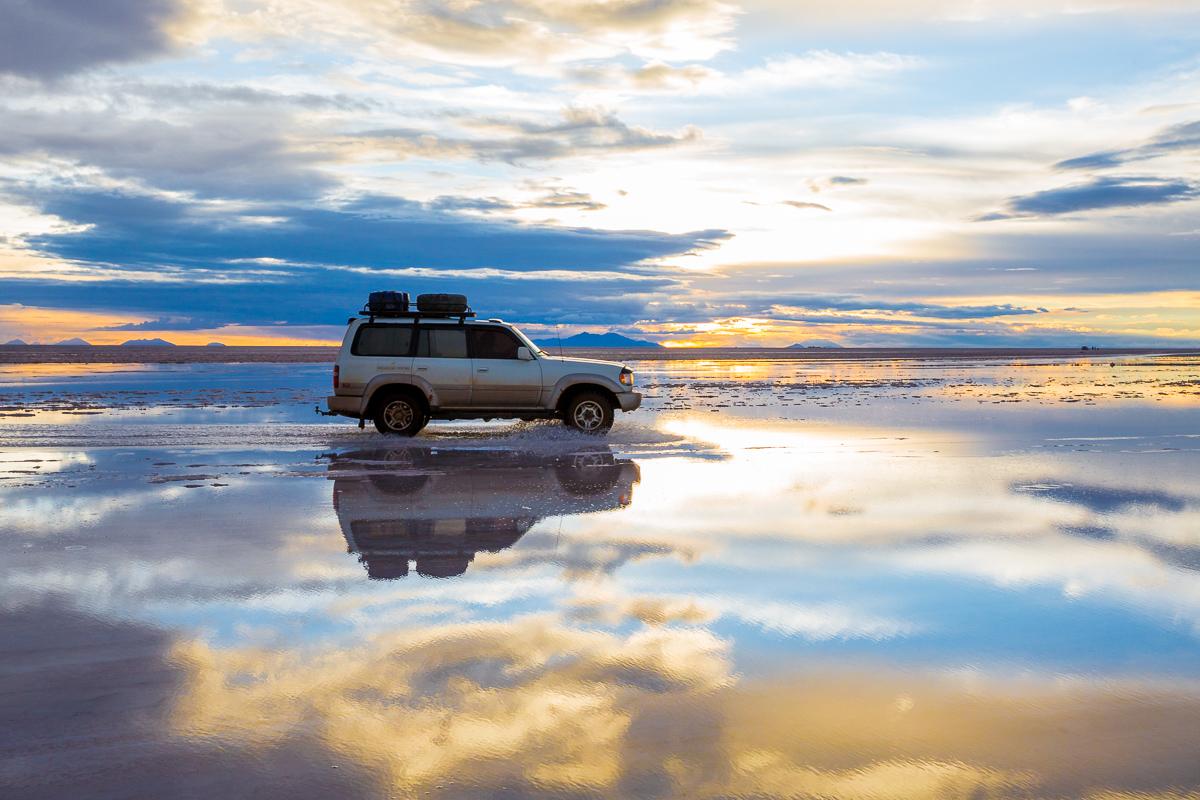 car-flooded-salar-de-uyuni-potosi-bolivia-salt-flats-sunset-sky-evening-wet-season-4x4-wheel-drive.jpg