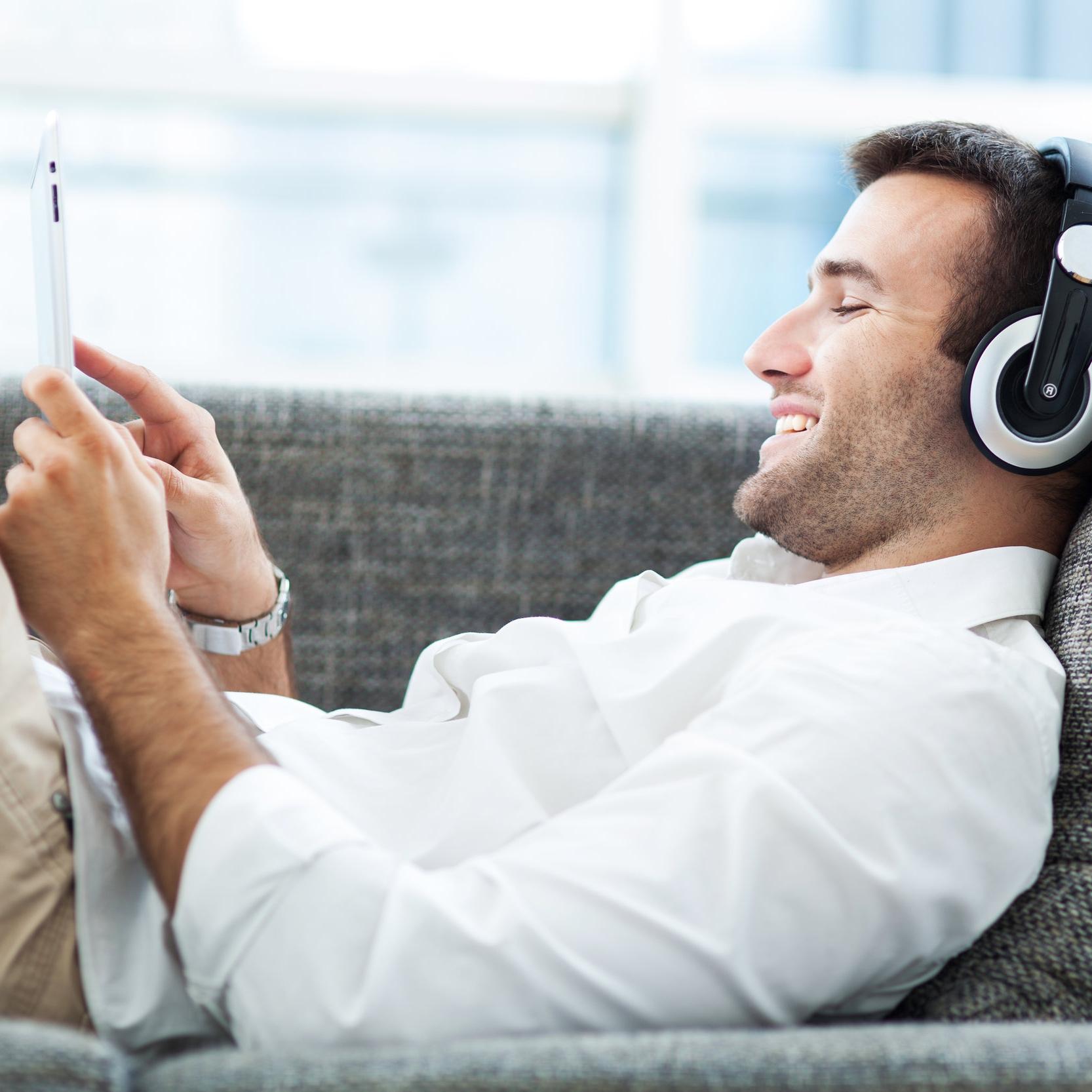 stock-photo-man-on-sofa-with-headphones-and-digital-tablet-142213039.jpg