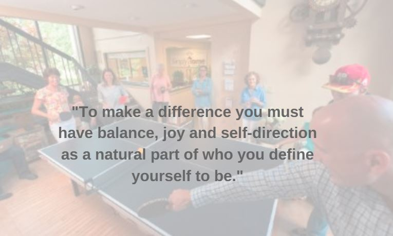 "A faded-out image of a group playing ping-pong, with the quote, ""To make a difference you must have balance, joy, and self-direction as a natural part of who you define yourself to be."""