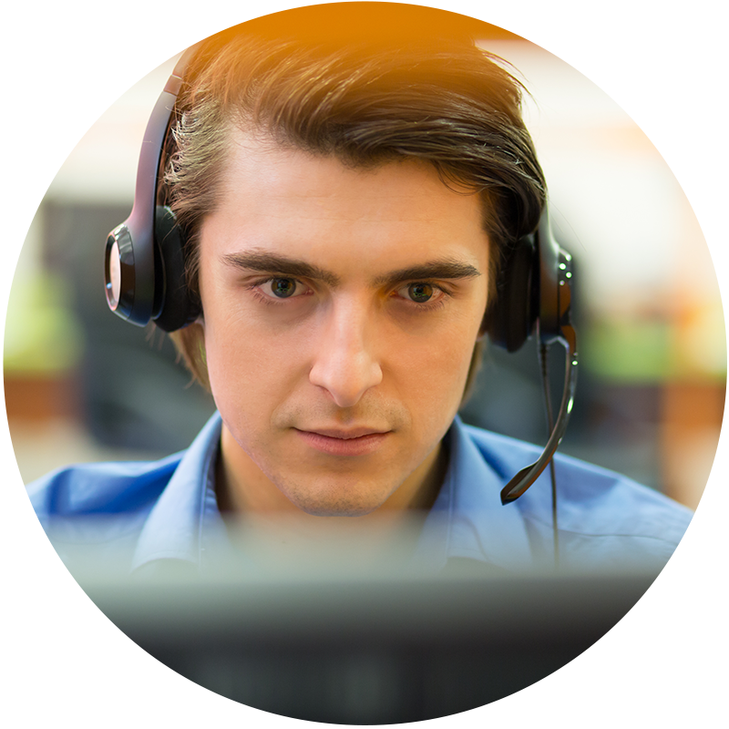 A man with a headset looks at a computer screen