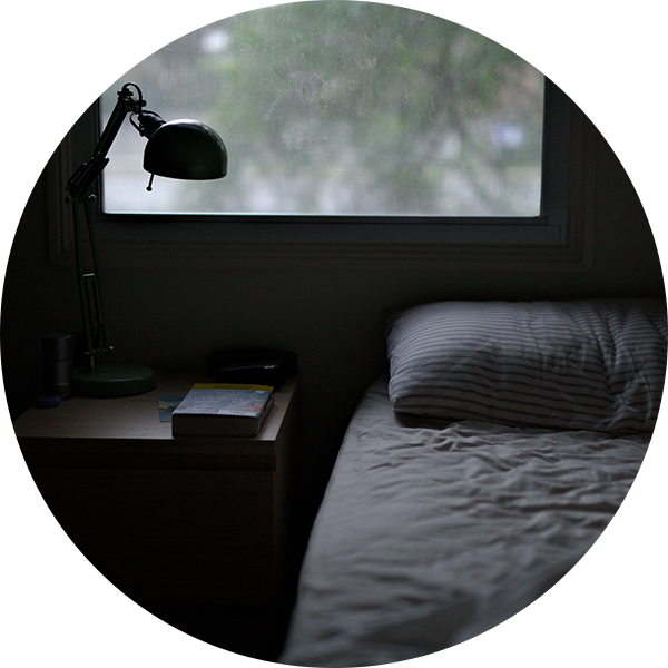 An image of a bed, a bedside table and lamp, with a window