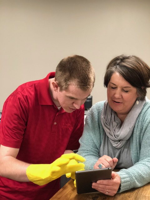 Bryan and Cameron look at Bryan's cleaning checklist on a tablet