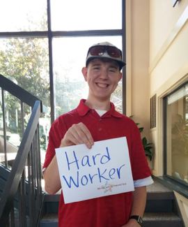 Bryan holds a sign that says Hard Worker on Hire My Strengths Day.png