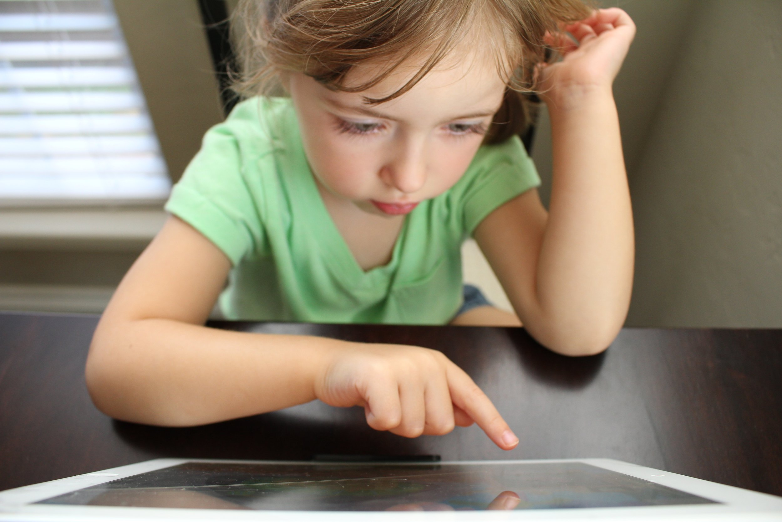 Image: A young girl points to a tablet screen as she is seated at a table. (Source: https://bit.ly/2UgPe8W)