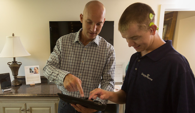 Image: SimplyHome Chief Development Officer Jason Ray stands and points to a tablet, demonstrating to a young man how to use the device to control lights in a living room environment. (Source: SimplyHome photos)