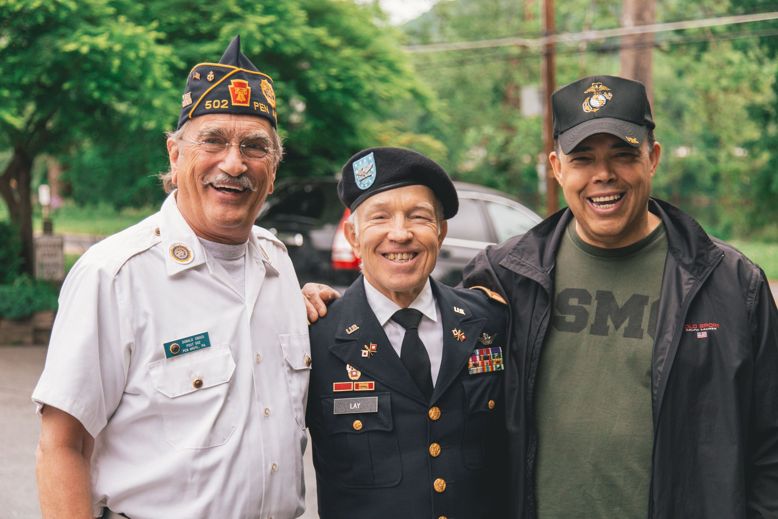 Three service members pose for a picture.  Source.