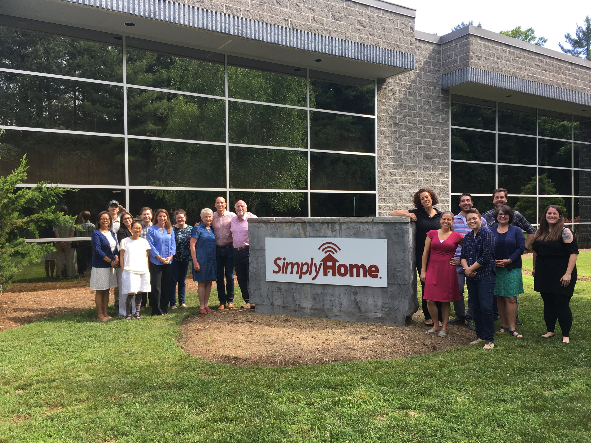 Members of the  Simply Home team pose for a picture outside the company's Asheville offices.
