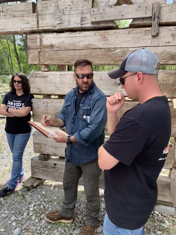 The teams from Barnwood Builders and David's Vision discuss the plan for David's log cabin .