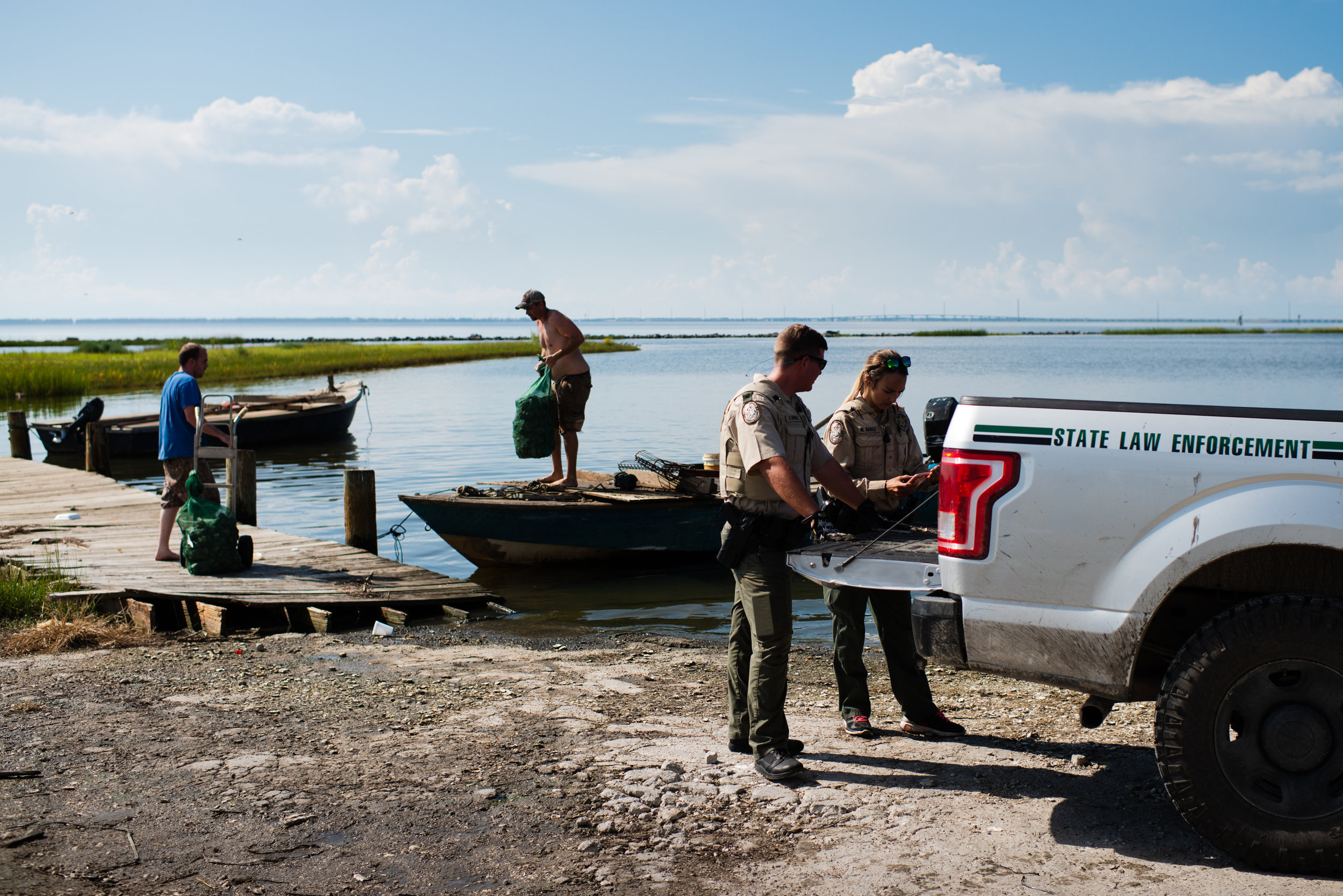 Florida State Law Enforcement agents inspect oyster boats arriving at a seafood wholesaler where they sell their catch. Due to the sharp decline in the oyster population of the bay, the state and local authorities have placed strong restrictions on oyster production. During summer months, oystermen can only work on the water from sunrise to 11am. They are only allowed a maximum (which they never reach) of two 50lbs bags per person and all oysters much be at least 3 inches. Cheating is common and fines are steep, $550 if caught.