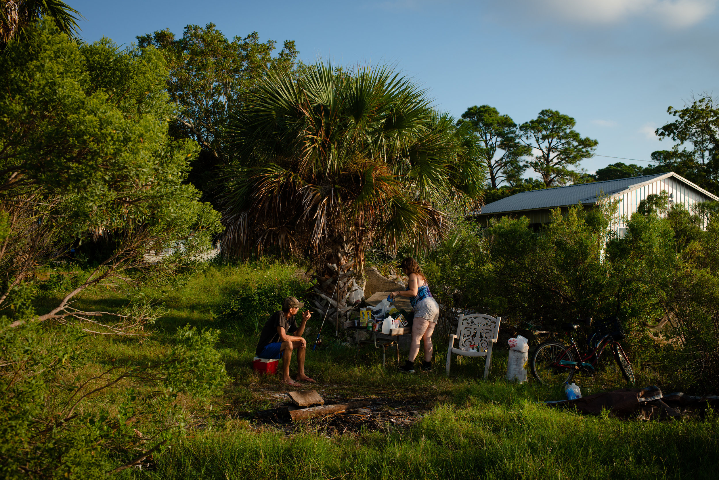 "Heather Petty, 42, and her boyfriend Fred Wilsey, 53, are sleeping on private land off the main road in Eastpoint. They have been homeless since 04 July, 2018. Fred has spent most his life, 38 years, living off the what the Apalachicola bay provides, Heather, who came to the area 10 years ago to care for her dying father joined Fred on the boat. Five years ago, because of smaller hauls, they quit harvesting oysters full-time and began cleaning rental properties on nearby Saint George Island, a popular tourist destination. When they began cleaning homes they would make combined $1500 a week, now $500 if they are lucky enough to find work. ""People come here because of oysters,"" said Fred. ""Now that there is a depletion of oysters, fewer people are coming here."" With little work and loss of their savings, Fred and Heather now sleep on the docks and have returned to fishing, not always legally, to survive. ""The water is all we have left,"" Heather said. ""You have to be a felon to eat around here. That is what they are turning us it into."""