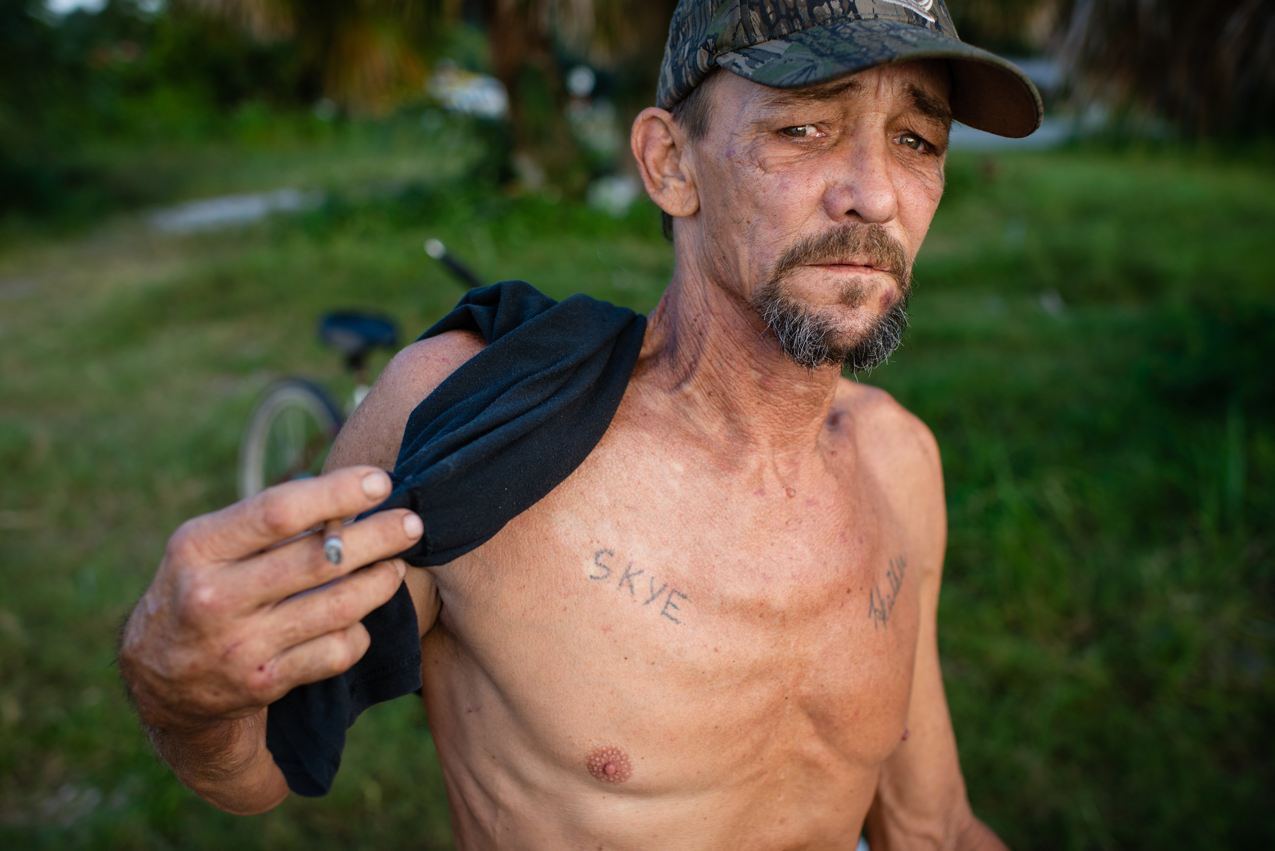 "On his chest Fred Wilsey, 53, has two tattoos, one for his daughter Skye and the other for his girlfriend Heather Petty. Fred and Heather have been homeless since 04 July, 2018. Fred has spent most his life, 38 years, living off the what the Apalachicola bay provides, Heather, who came to the area 10 years ago to care for her dying father joined Fred on the boat. Five years ago, because of smaller hauls, they quit harvesting oysters full-time and began cleaning rental properties on nearby Saint George Island, a popular tourist destination. When they began cleaning homes they would make combined $1500 a week, now $500 if they are lucky enough to find work. ""People come here because of oysters,"" said Fred. ""Now that there is a depletion of oysters, fewer people are coming here."" With little work and loss of their savings, Fred and Heather now sleep on the docks and have returned to fishing, not always legally, to survive. ""The water is all we have left,"" Heather said. ""You have to be a felon to eat around here. That is what they are turning us it into."""