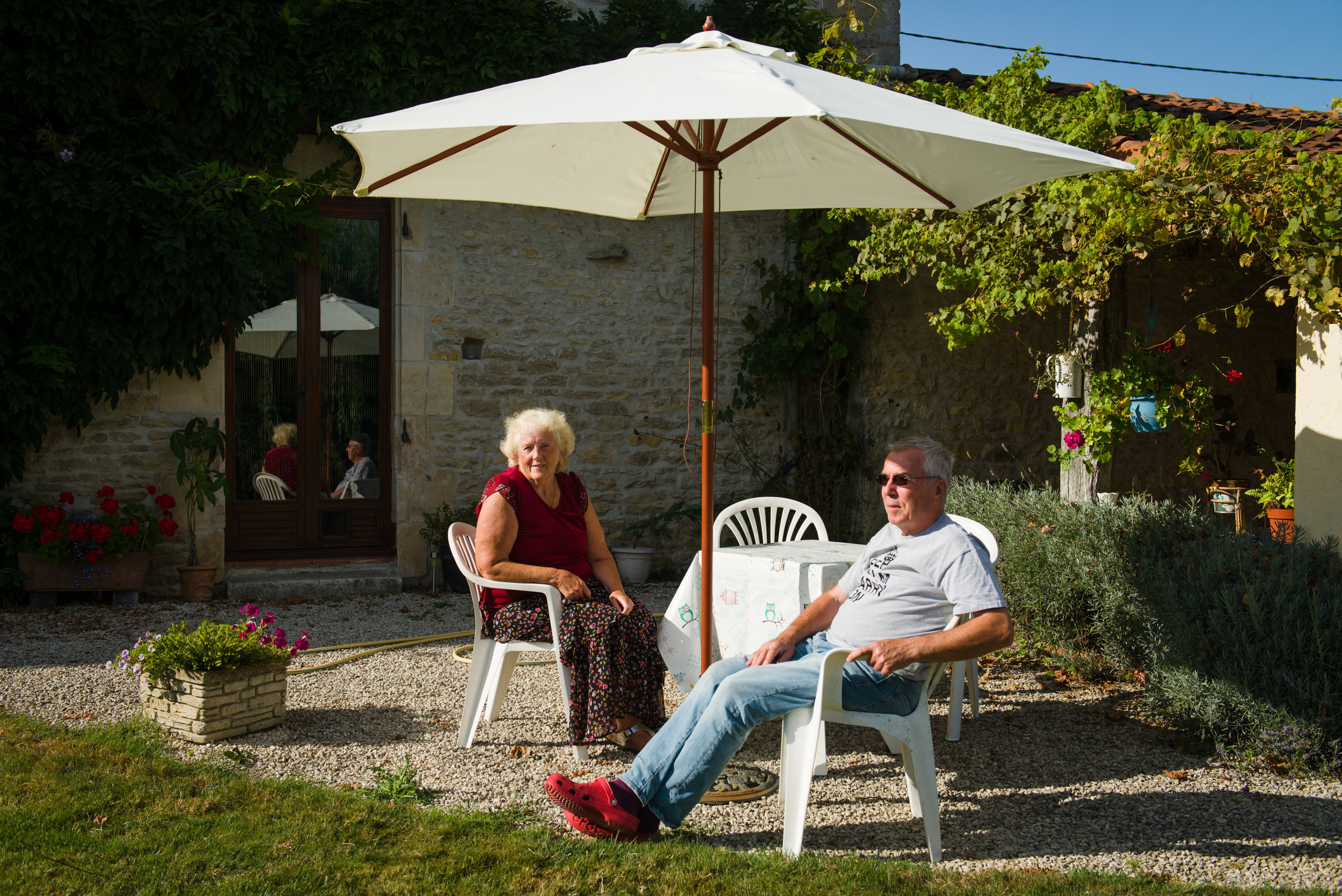 """Dave and Norma Spokes pose for a portrait in their backyard garden outside the town of Mauprevoir, France. Dave and Norma retired to France in 2010 moving from the UK. """"We have friends living here & we visited several times and we liked the lifestyle, we liked the people, the countryside, the type of homes you can get here,"""" Dave said. """"We found that we could sell our property in England and buy something substantially larger with a lot more land over here. And, generally speaking, the cost of living here is less than it is in England, so your pension tends to go further."""" Since arriving in France, Norma has been diagnosed with cancer and is being treated in France. Although Brexit has created some concern in how it could affect UK pensioners access to care in France, Dave and Norma believe they can continue to benefit from the French system. """"I don't think there will ever be a situation where anyone says we're not going to treat you because you are British. There could be a situation where they say 'well will continue to treat you but you will need extra insurance'. And it's a question of whether people can afford that. If the UK government gets their act together and starts negotiating properly. There is a reasonable chance we come out of this with most of our rights in tact."""""""