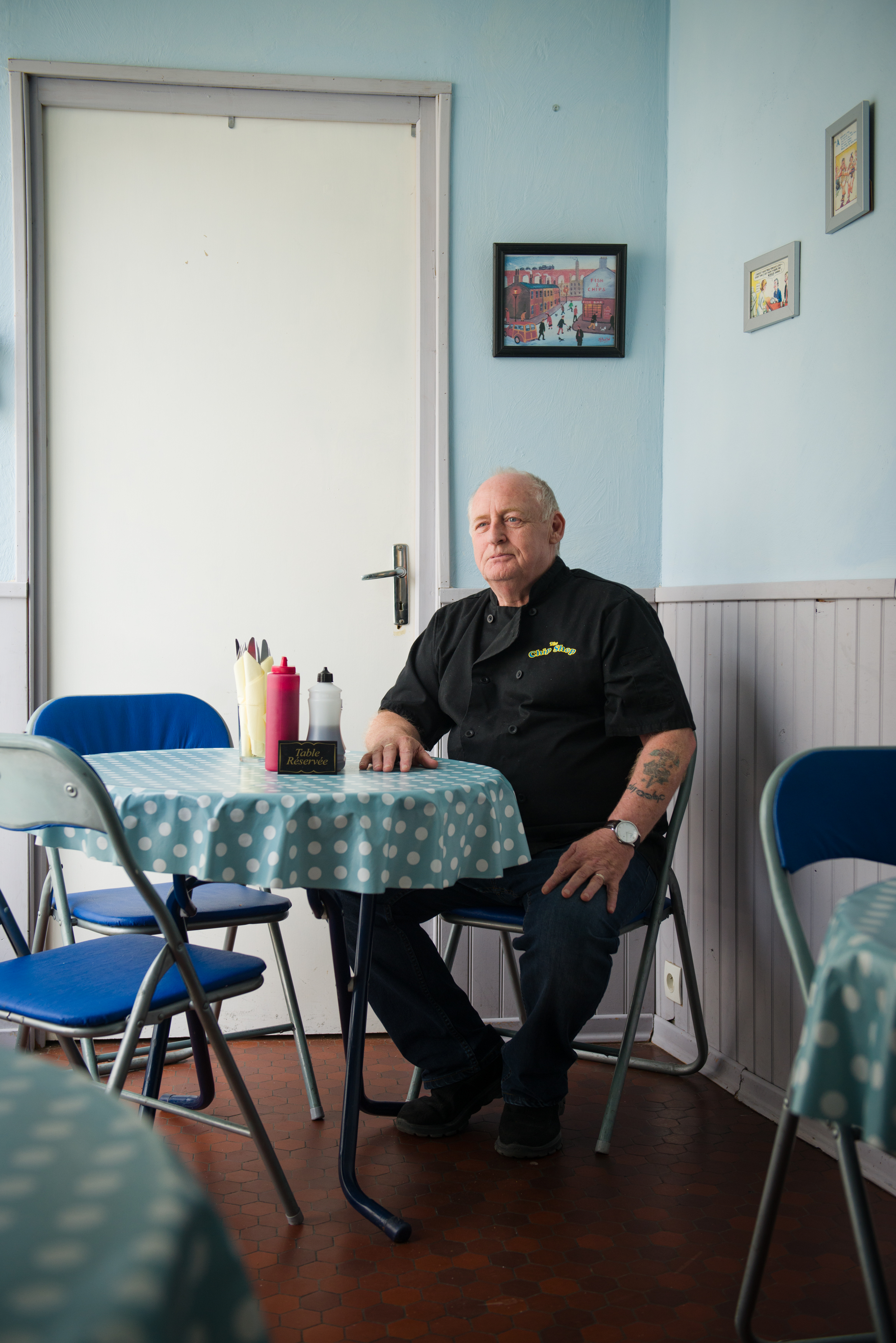 """Chris Middleton, 62, in The Chip Shop, a fish and chips restaurant he runs with his wife in Confolens, France. Chris has lived & worked in France for 12 years, he has a Carte Vitale (french healthcare) and when he retires in a couple years he will collect a French pension. """"They [English pensioners] don't take anything from the state, but they contribute with taxes and everything else. I think the main problem is going to be healthcare for the people who are retired who don't know whats going to happen with that yet. We are going to be ok because we worked here, so we have a carte vitale so we get all the benefits you have with that."""""""