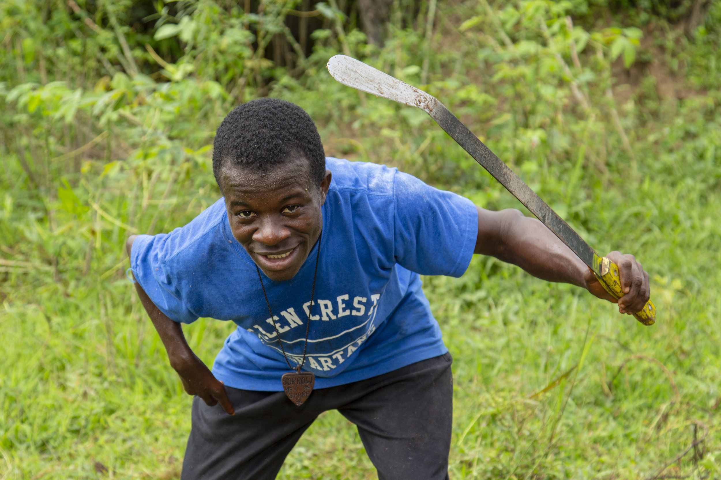 "Matthew is ""brushing"" on the farm. Brushing is the Liberian term for cutting the grass."