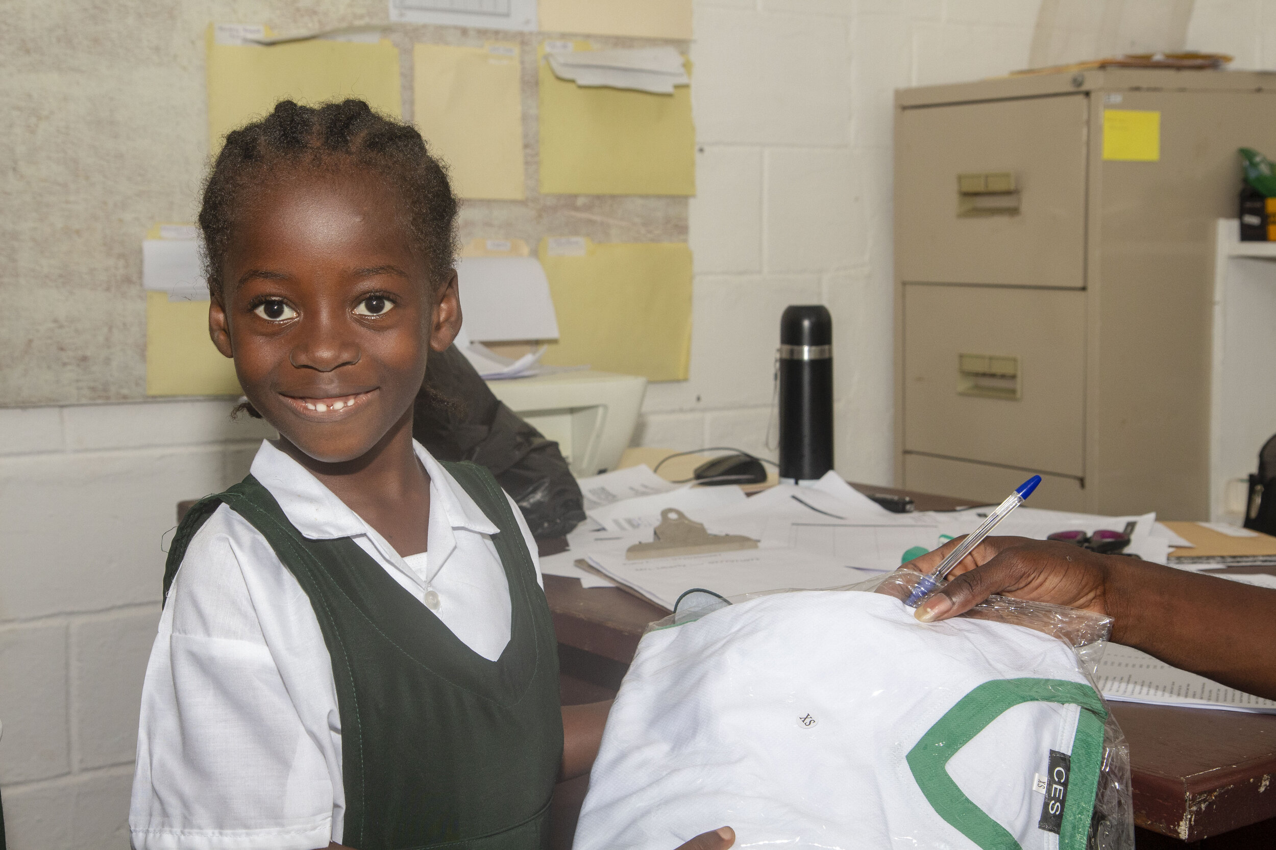One young student is happy to receive her brand-new P.E. uniform.
