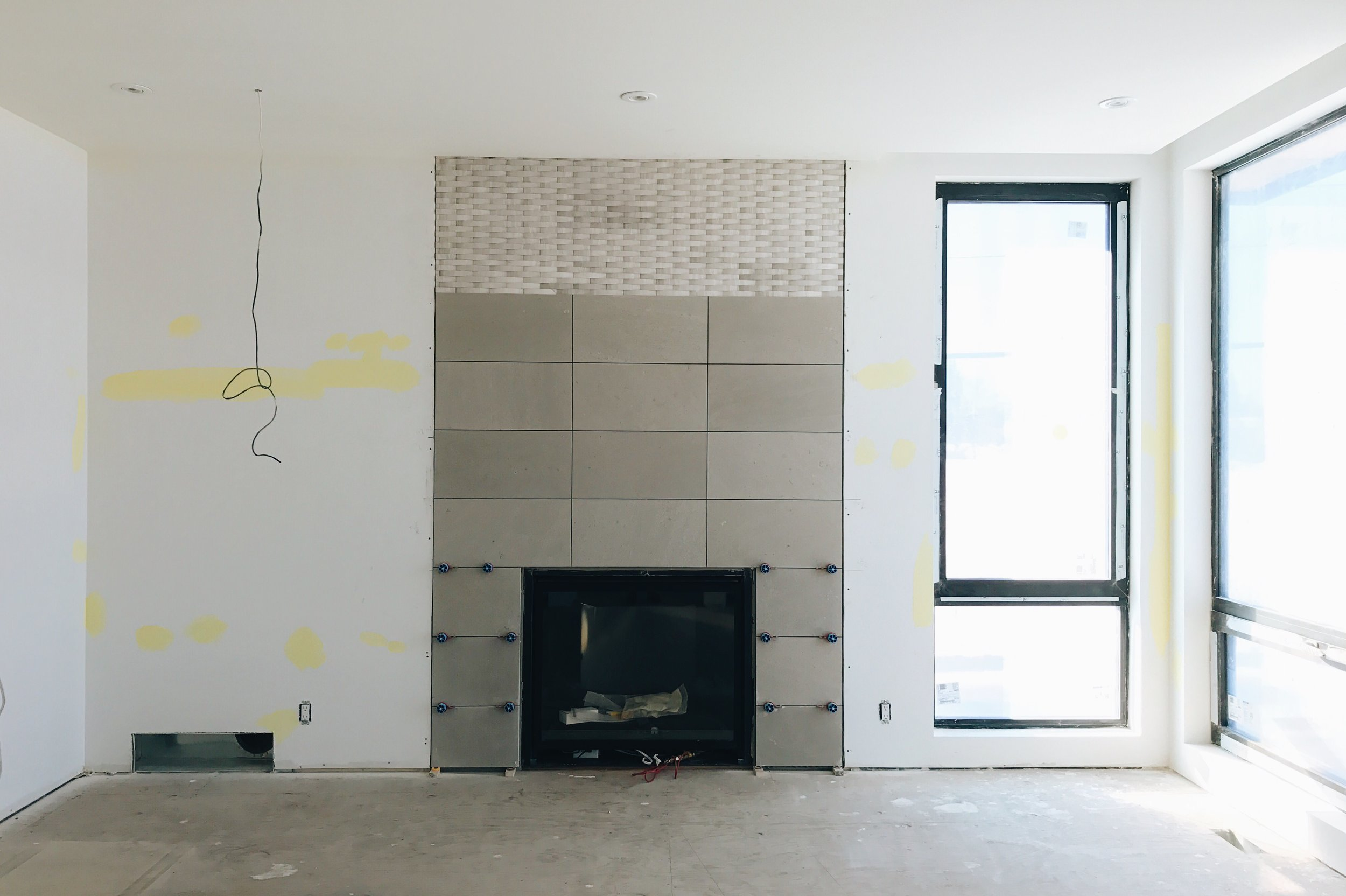 The fireplace wall is near completion and hardwood is ready to be installed. On a side note...these windows are stunning.