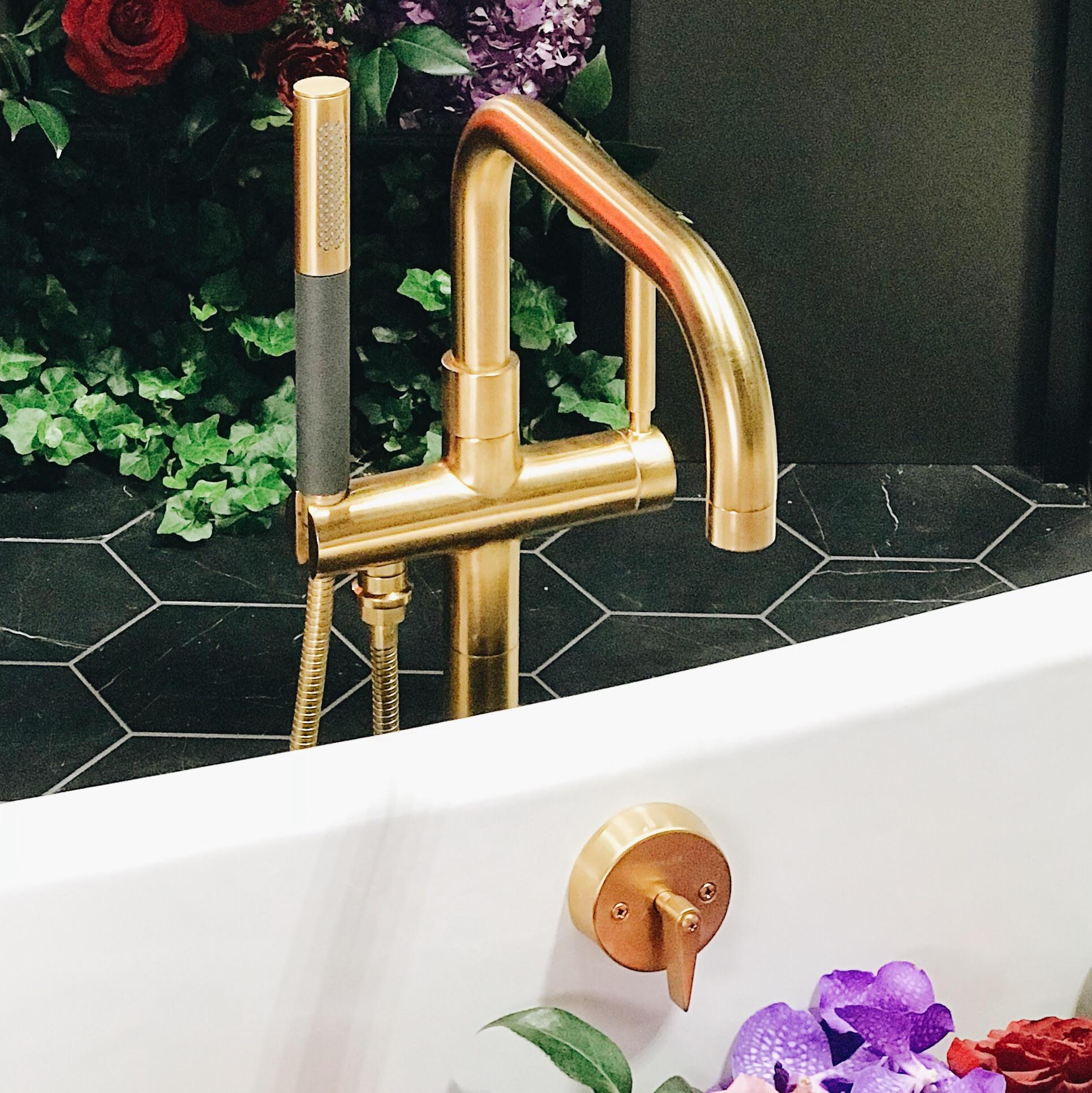 Kohler's   Stillness   tub filler in brass with wand in black.