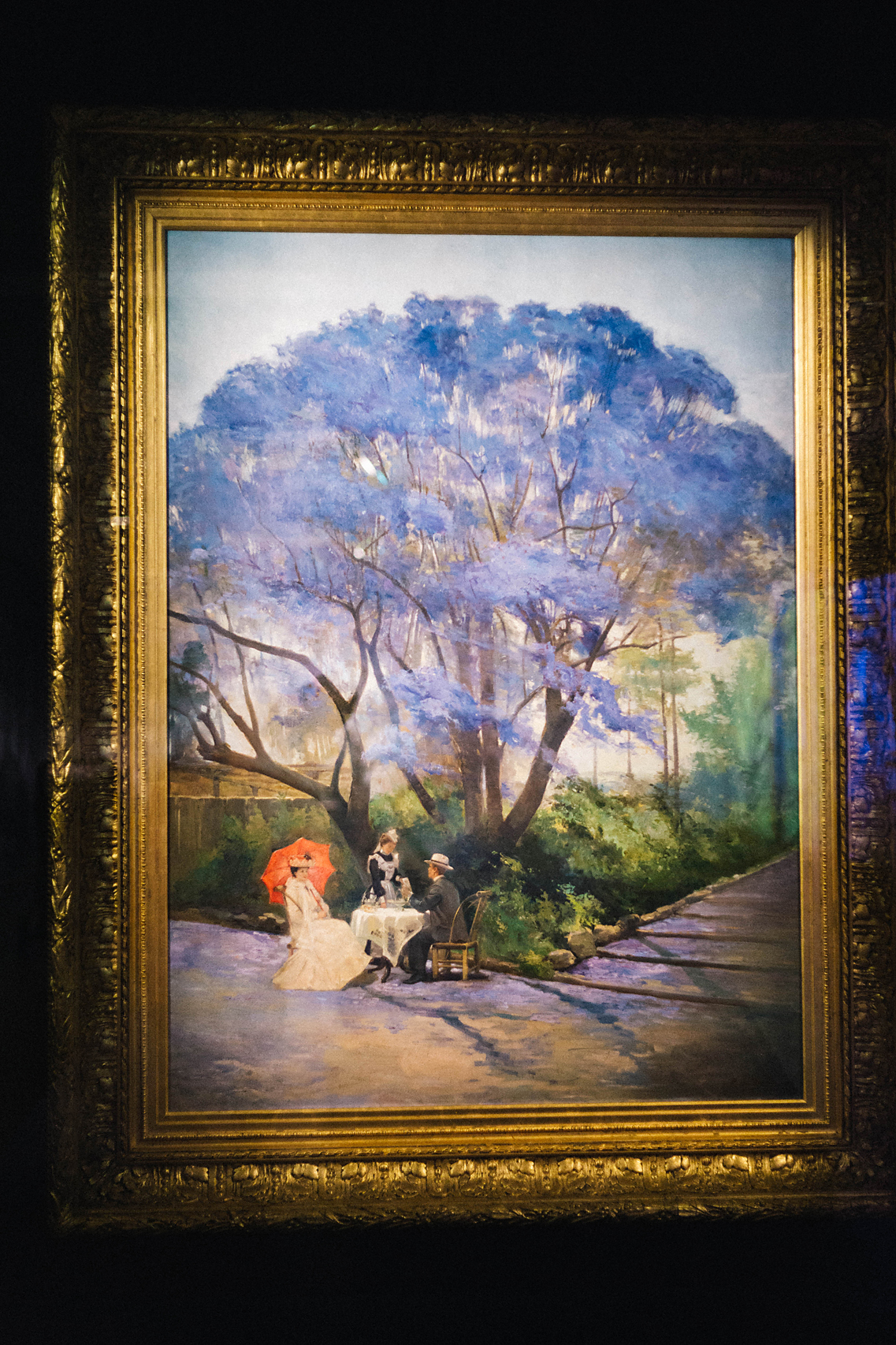 "Queensland Art Gallery; "" Under the Jacaranda "" by R Godfrey Rivers. Here is part of the description for this painting: ""Completed 13 years after Godfrey Rivers arrived in Australia,  Under the jacaranda  1903 offers a view of early twentieth-century life in Brisbane, with the subject reflecting a popular genteel European tradition of 'taking tea' in an attractive outdoor setting. The work depicts the artist and his wife, Selina, under the shade of a jacaranda tree in full bloom in the Brisbane City Botanic Gardens. Rivers captures the majestic form of the tree, emphasising its distinctive colour with the contrasting green vegetation and the sparkling accent of the red umbrella"". ( Poppy & Sage Photography )"