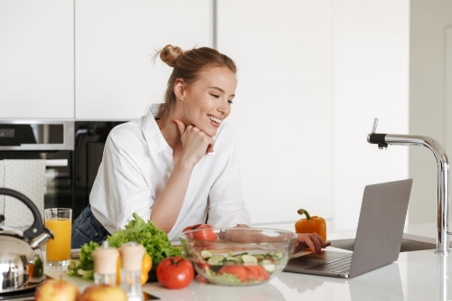 photodune-22282191-happy-young-pretty-woman-using-laptop-computer-cooking-xxl.jpg