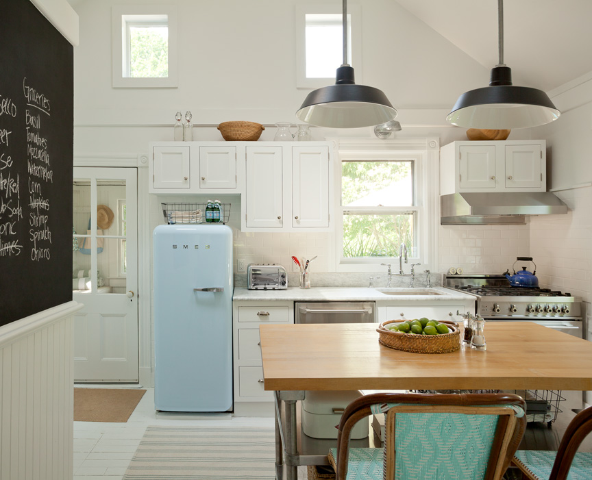 The vintage -looking powder blue Smeg refrigerator and the built-in chalkboard make the kitchen feel playful and casual, the perfect family gathering spot.