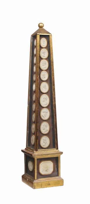 An giltwood obelisk mounted with 45 19th Century Grand Tour plaster intaglios.