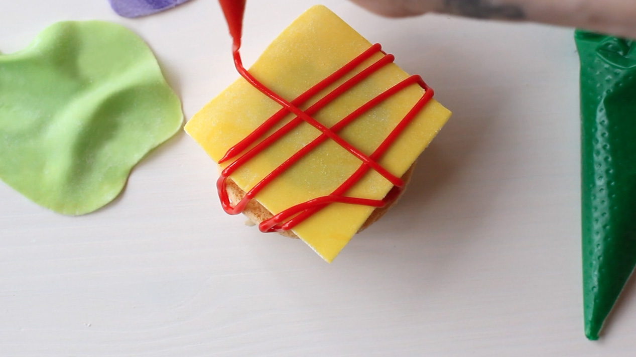 Step 4: Pipe condiments onto cheese slice.