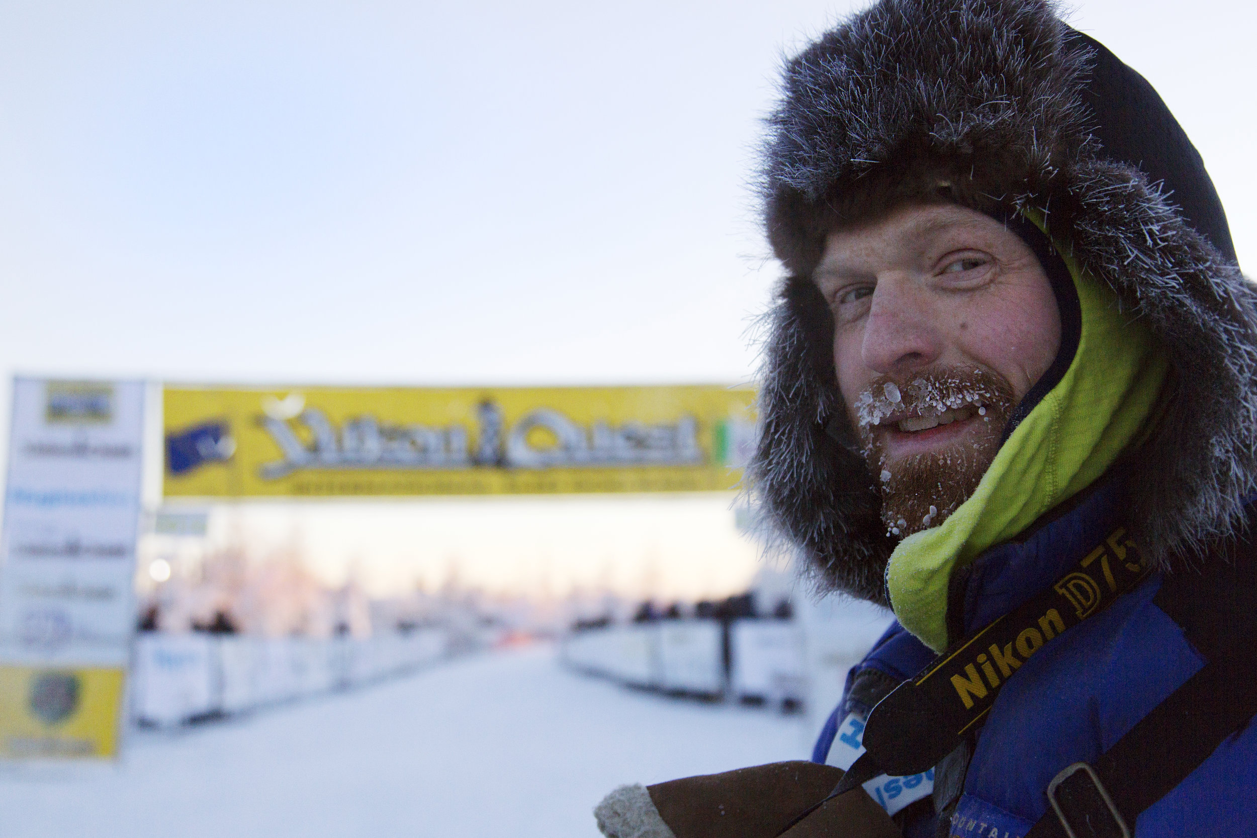 Official Yukon Quest photographer, Seth Adams, stands at the start line on day one of the race outside of the Morris Thompson Visitor Center in downtown, Fairbanks, AK. When Adams isn't photographing the quest, he works a freelance adventure writer and photographer in Fairbanks, Alaska. He specializes in outdoor adventure journalism and first-person trip reports. (c) Sarah Manriquez 2018