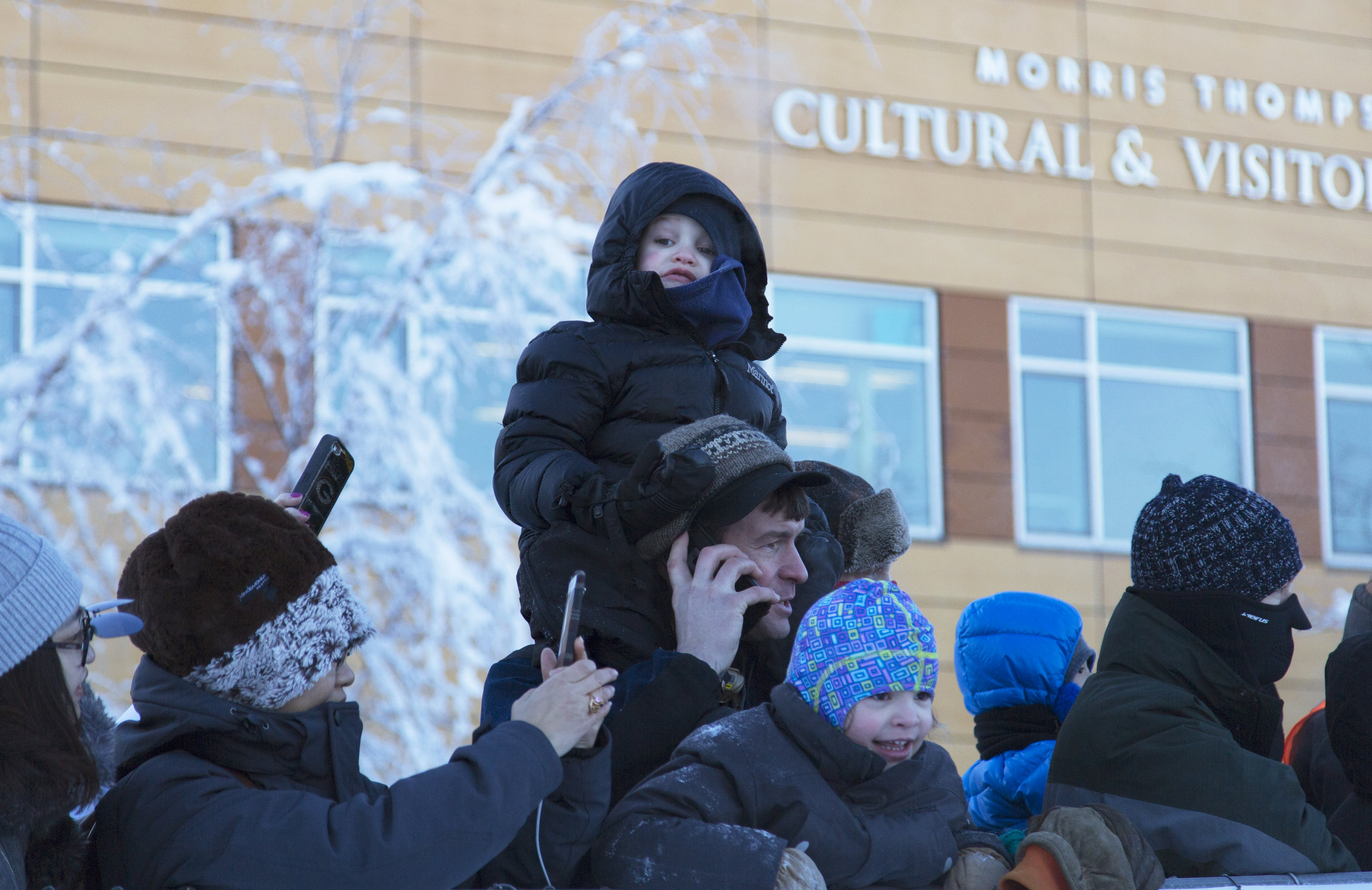 Young spectator gets a better view atop his father's shoulders. n some areas spectators were behind several rows of people. Crowds packed the barricades at the start line of the 2018 Yukon Quest despite the freezing temperatures of -20F. Folks were bundled in their winter gear and most armed with cameras. (c) Sarah Manriquez 2018