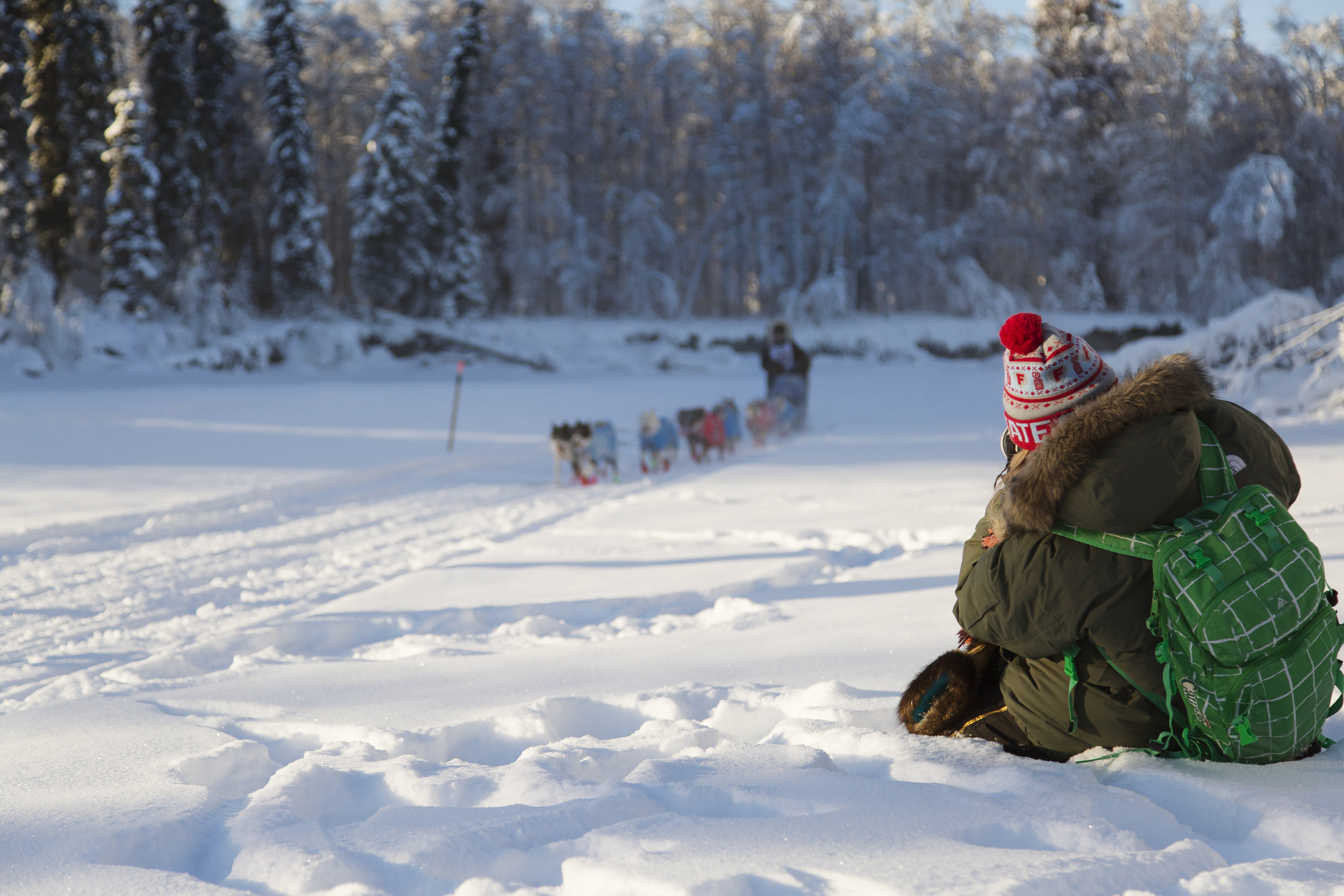 UAF photography student, Ruby Campbell sits in the snow and photographs #22, Ike Underwood as he makes his way down the frozen Chena River on the first day of the Yukon Quest. (c) Sarah Manriquez 2018