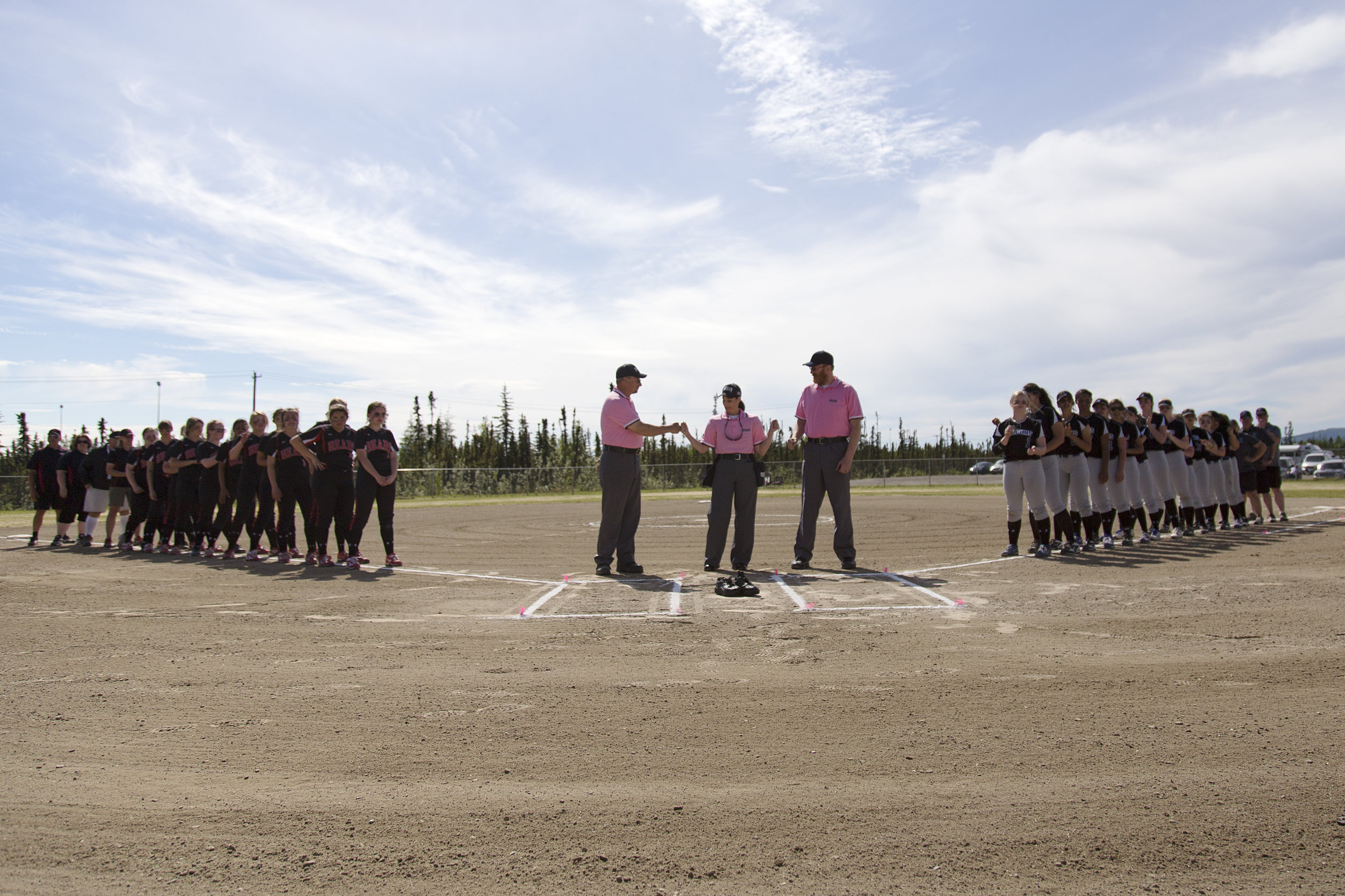 Juneau Douglas softball team and coaches (left) and the Thunder Mountain softball team and coaches (right) and umpires (center) line up before the start of the final game for the 2017 State Championship title on Saturday, June 3rd in the South Davis Park Complex in Fairbanks, AK. Sarah Manriquez/ Juneau Empire