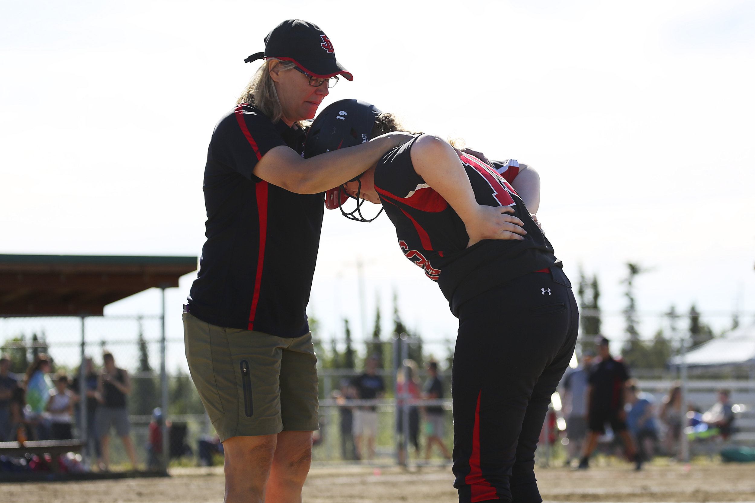 Juneau Douglas, Mia Loree (19) (right) grabs her back in pain and leans into her coach, Annie Kincheloe (left) for support after trying to sprint to first base in a game against Thunder Mountain on Saturday, June 3rd at the Softball State Championships in the South Davis Park Complex in Fairbanks, AK. Kincheloe walked Loree off the field and escorted to her to dugout. Sarah Manriquez/ Juneau Empire