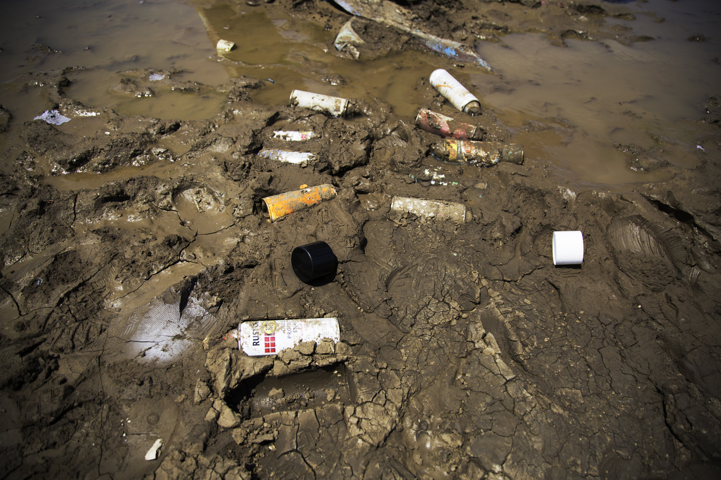 Spray paint cans are littered all over the ground, abandoned and half buried in the dirt and mud around the vehicles.