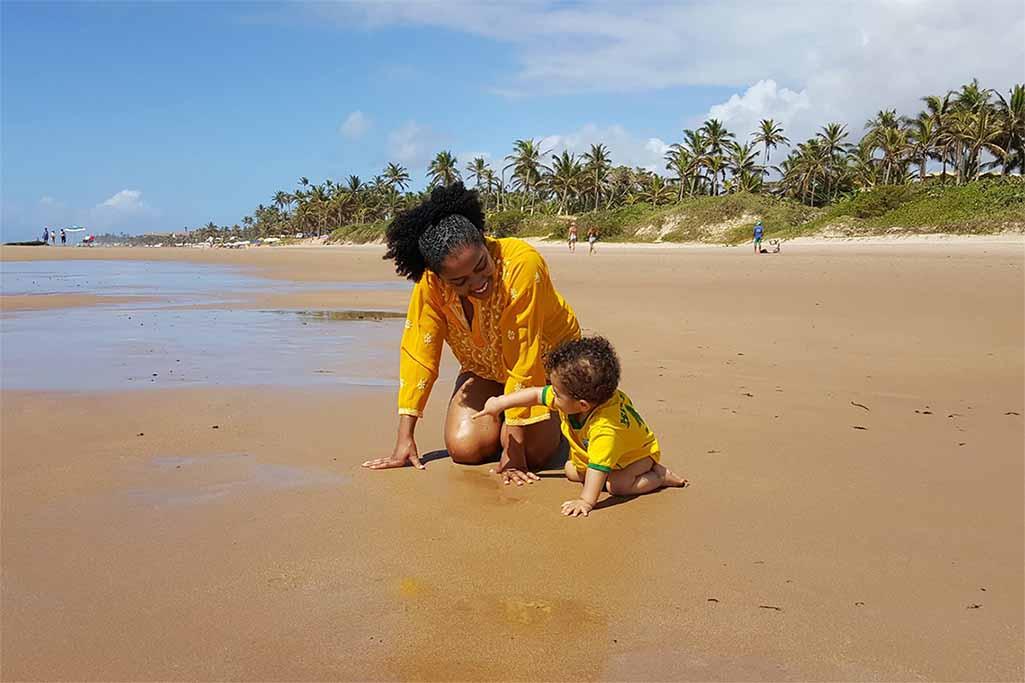 A jornalista Iana Borges trouxe o filho ao Brasil em seu primeiro aniversário de vida. Assim, na praia, em terra bem firme, Iana se sente muito melhor