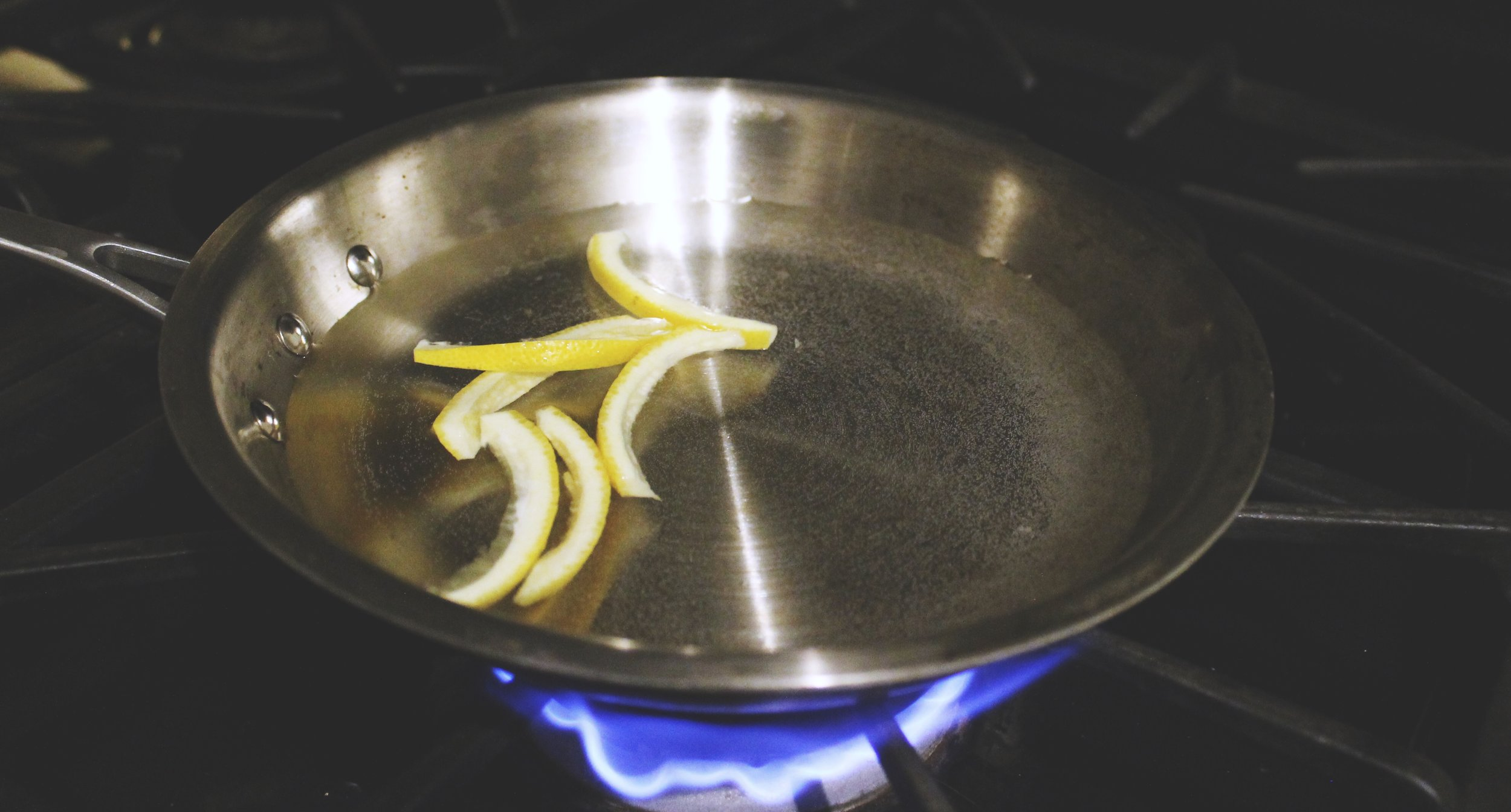 Cover peels with water in a pan. Bring to a boil and simmer for 1 minute. Drain and repeat 2x.