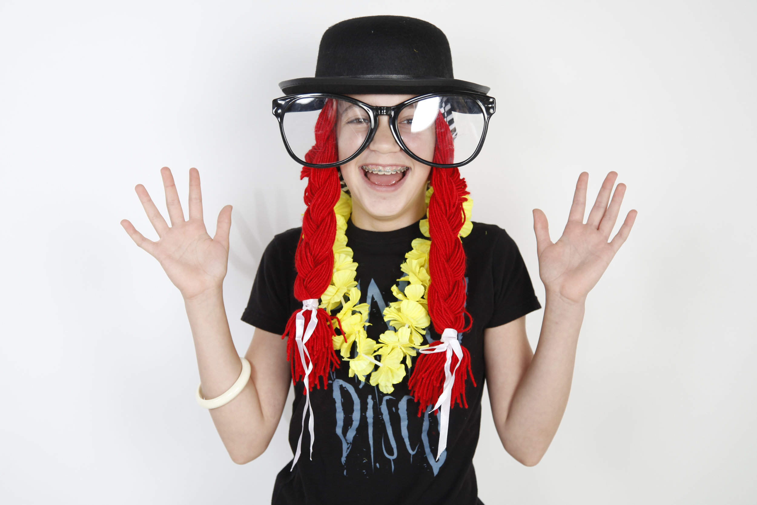 Young boy waving his hands, wearing costume props- oversized glasses and hat and braids.