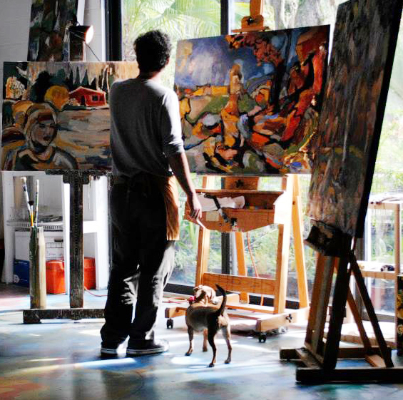 John Joseph Graham standing in front easels with paintings on them.