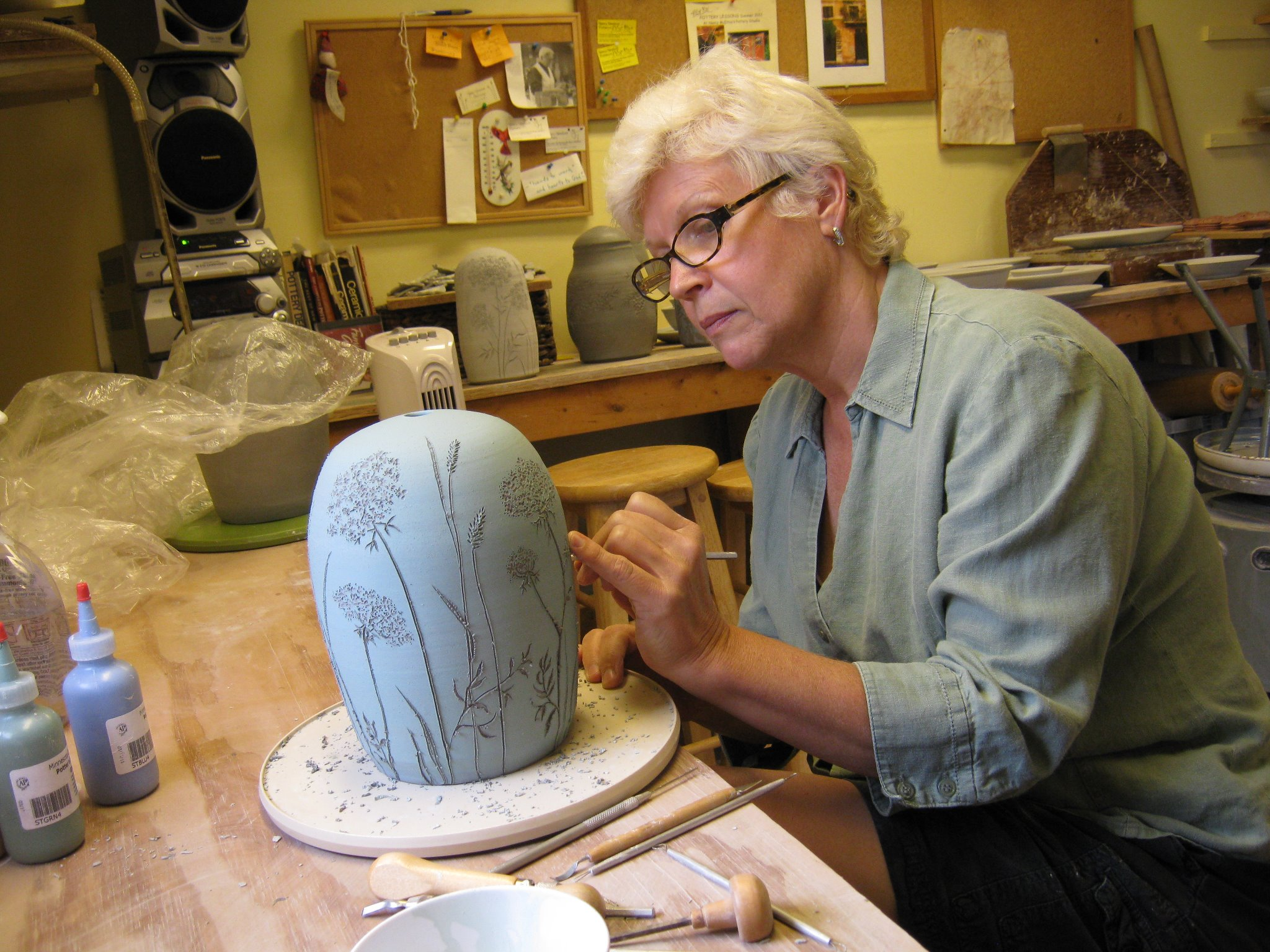 Portrait of Nancy Newlove McElroy painting a pottery piece.