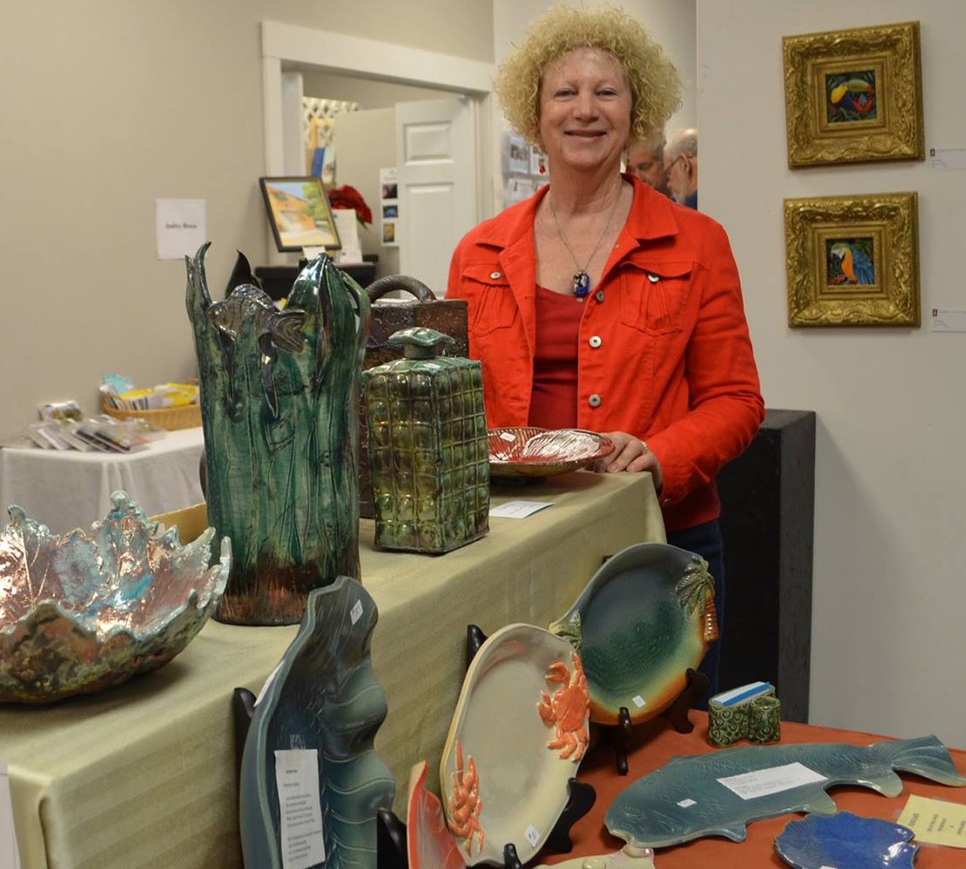 Portrait of a Robinn Wren standing next to various pottery pieces all on display in a gallery.