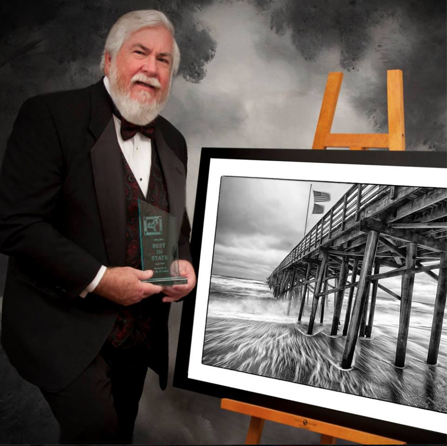 Photo of Joe Campanellie holding an award, standing in front of one of his photographs