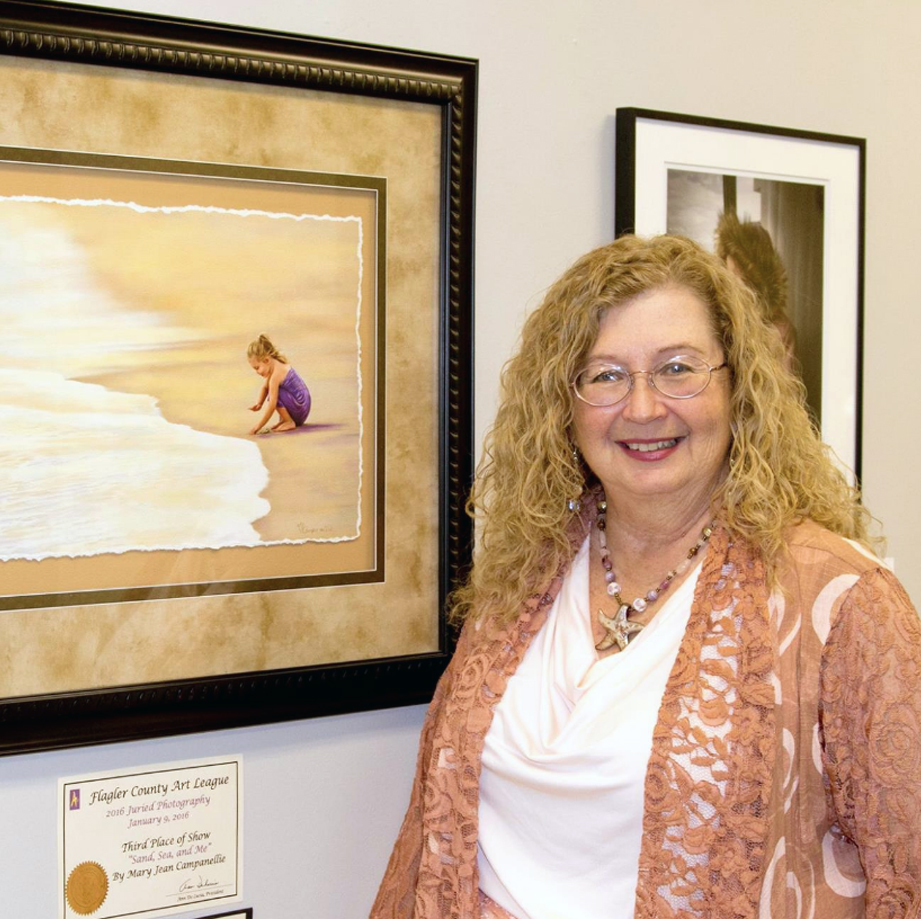 Portrait of Mary Jean Campanellie standing in front of one of her photographs.