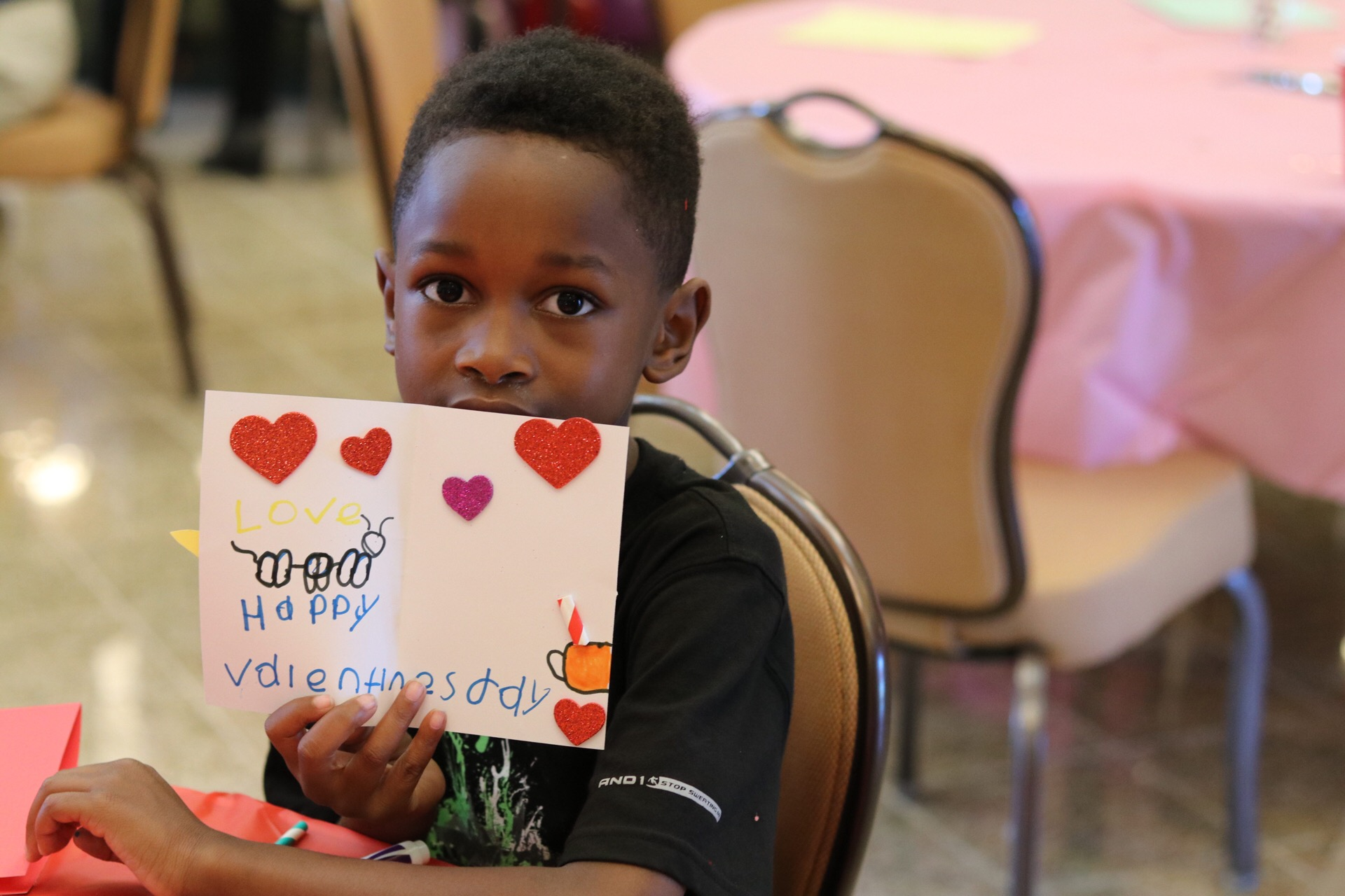 Young boy holding up a Happy Valentine's Day card.