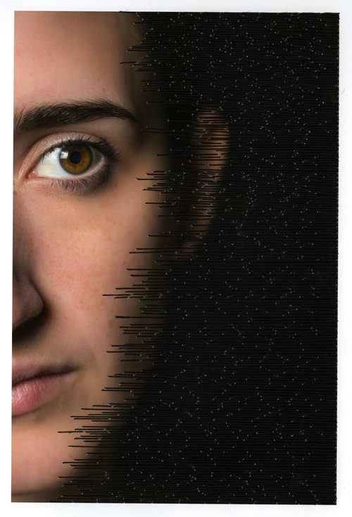 Close-up of a woman's face, there is thread that was stitched over part of the image